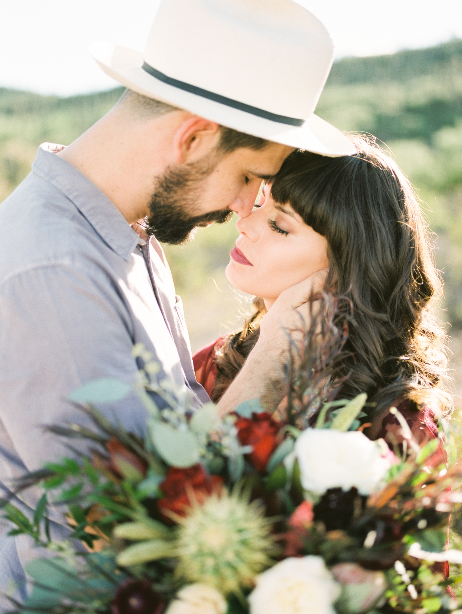 hipster couple about to kiss at their tucson desert elopement Stunning tablescape by Le Champagne Projects captured by Tucson film wedding photographers Betsy & John on Portra 800