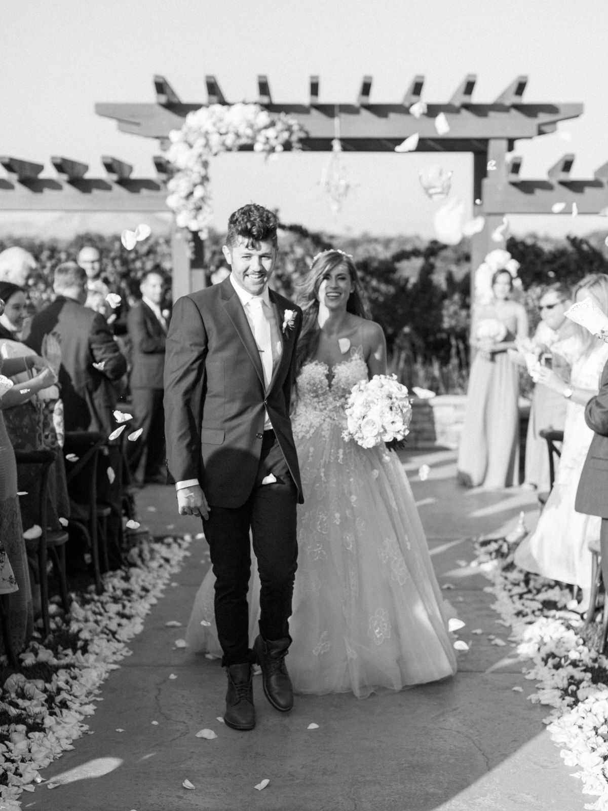 Bride & groom walking down the aisle, showered by flower petals! What a great exit. Harrison & Jocelyne's gorgeous Temecula wedding at Wiens Family Cellars captured by Betsy & John Photography