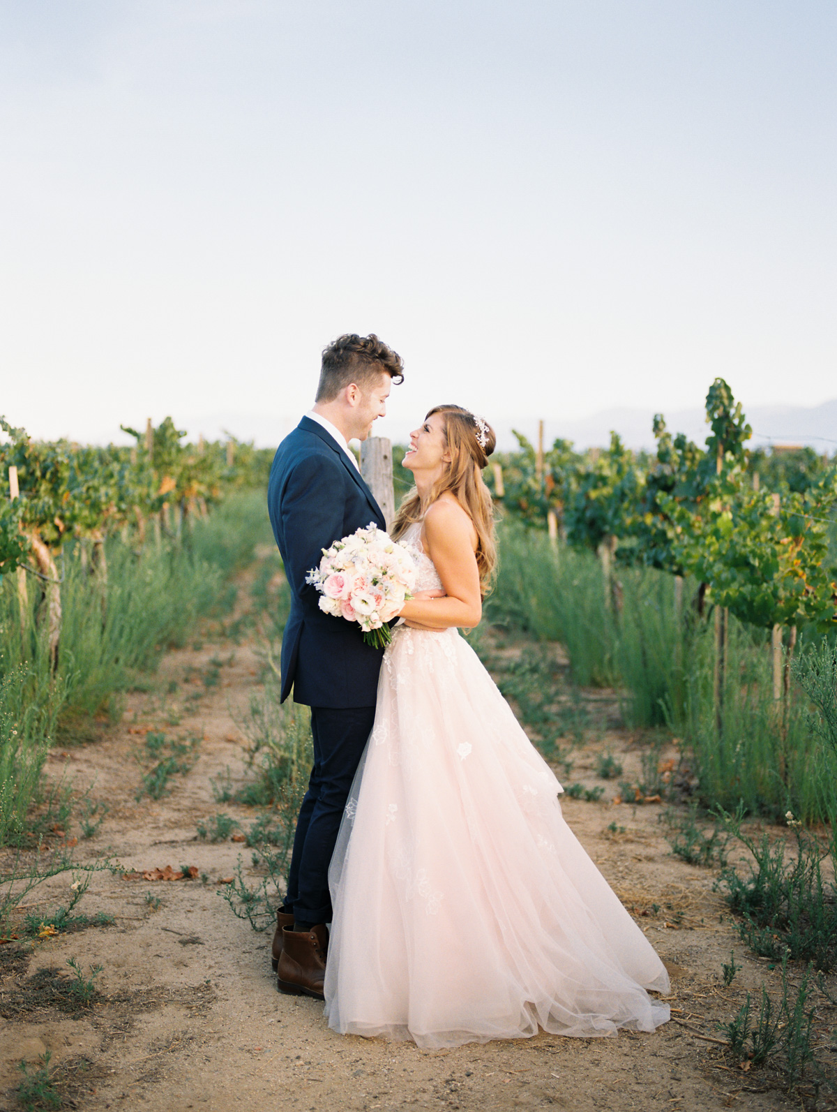 Bride & groom laughing at each other | Harrison & Jocelyne's gorgeous Temecula wedding day at Wiens Family Cellars captured by Temecula wedding photographers Betsy & John