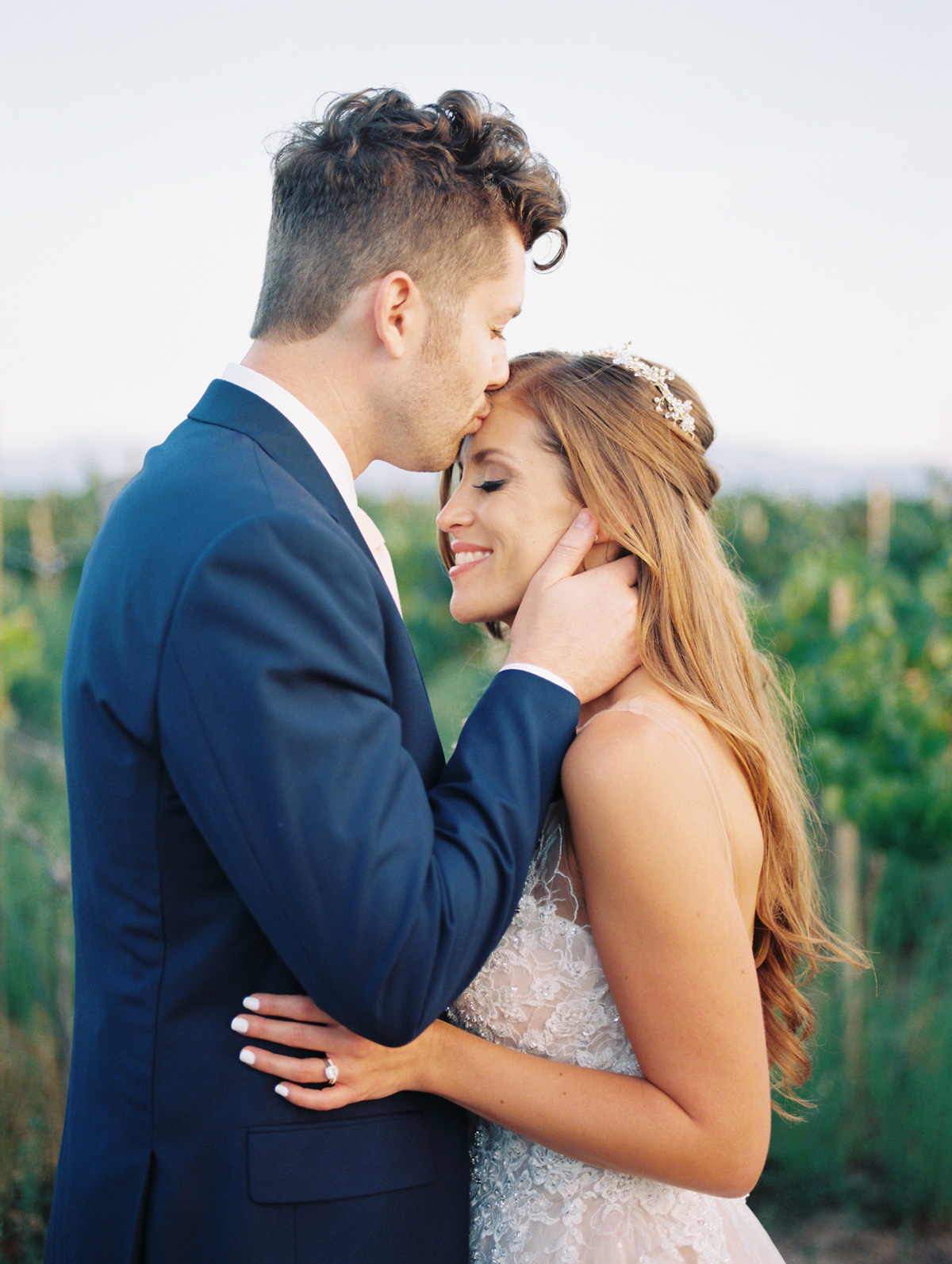 Groom kissing bride on the head, redhead bride smiling |Harrison & Jocelyne's gorgeous Temecula wedding day at Wiens Family Cellars captured by Temecula wedding photographers Betsy & John