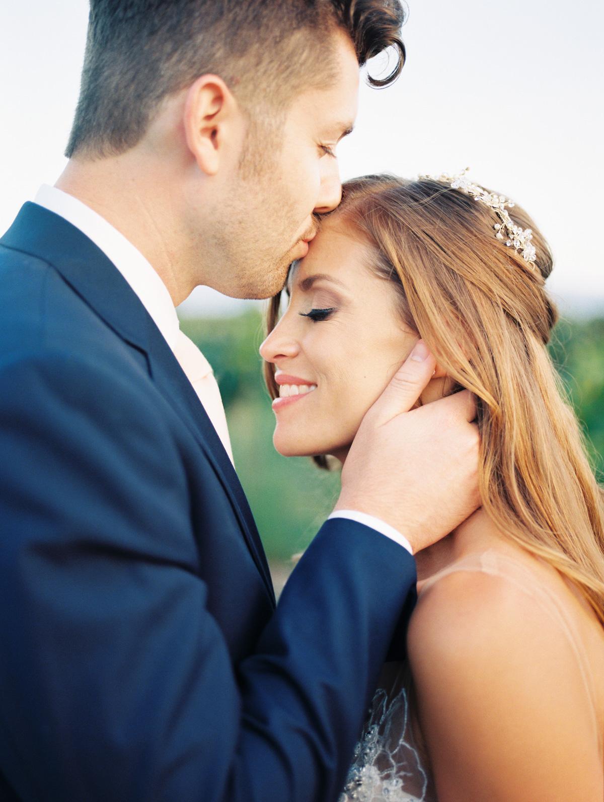 Groom kissing bride's head, bride smiling |Harrison & Jocelyne's gorgeous Temecula wedding day at Wiens Family Cellars captured by Temecula wedding photographers Betsy & John