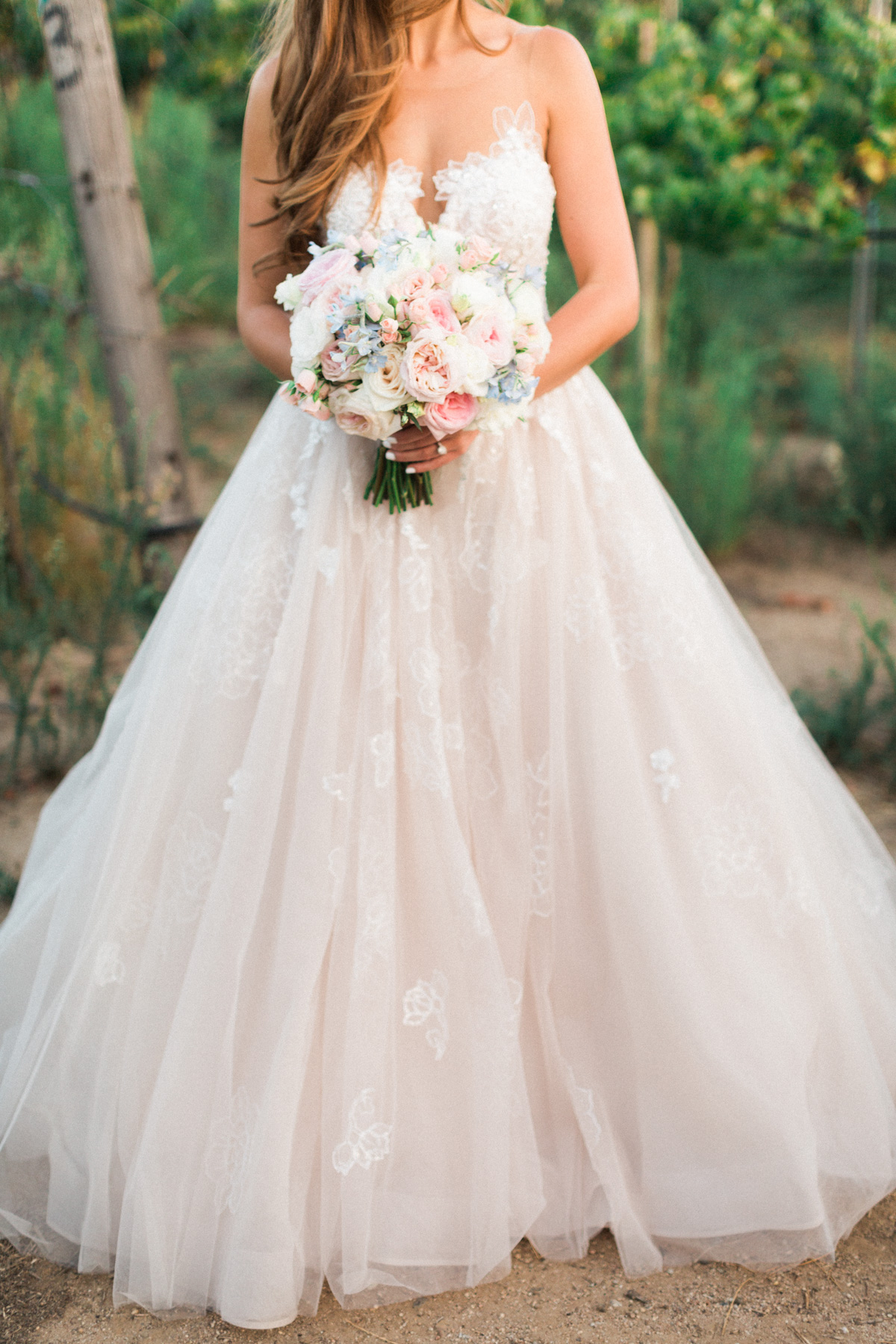 Gorgeous blush wedding gown by Essence of Australia with a blush bridal bouquet by Soiree Design & Events captured by Temecula wedding photographers Betsy & John