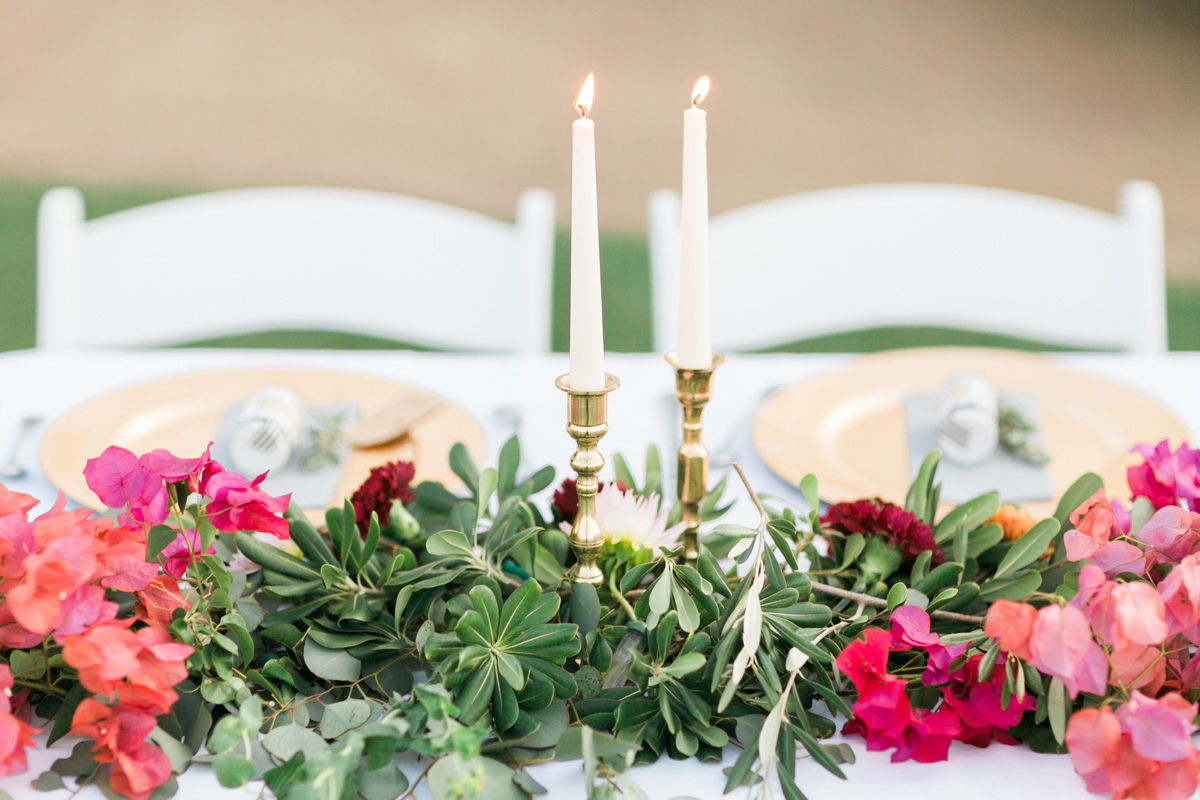 Brass candlesticks, greenery and bougainvillea on the head table