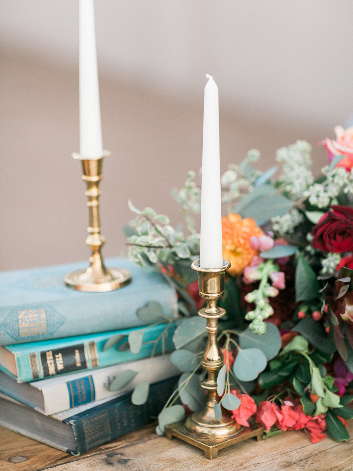 Charming wedding details, vintage books and brass candlesticks with draping greenery and florals