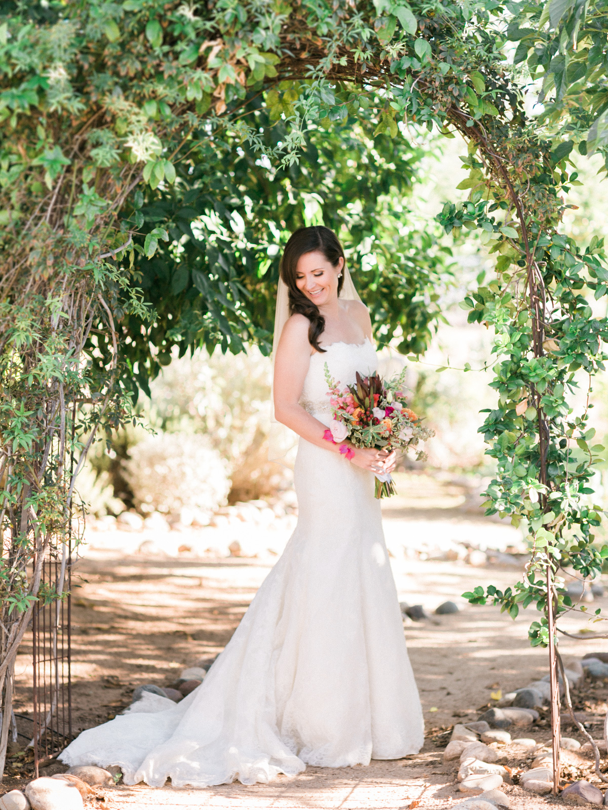 Gorgeous classic bride under green archway captured by Phoenix wedding photographers, Betsy & John