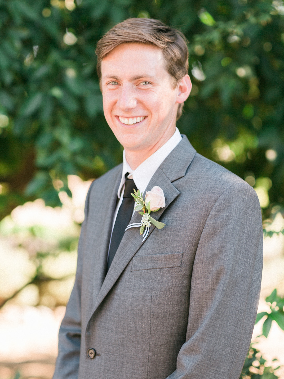 Handsome groom smiling at camera with blush boutonniere