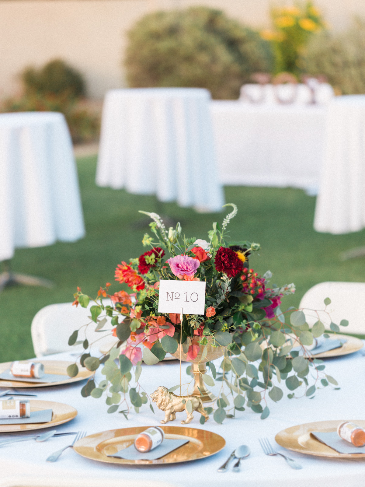 white tables with gold chargers and beautiful green and jewel toned centerpieces