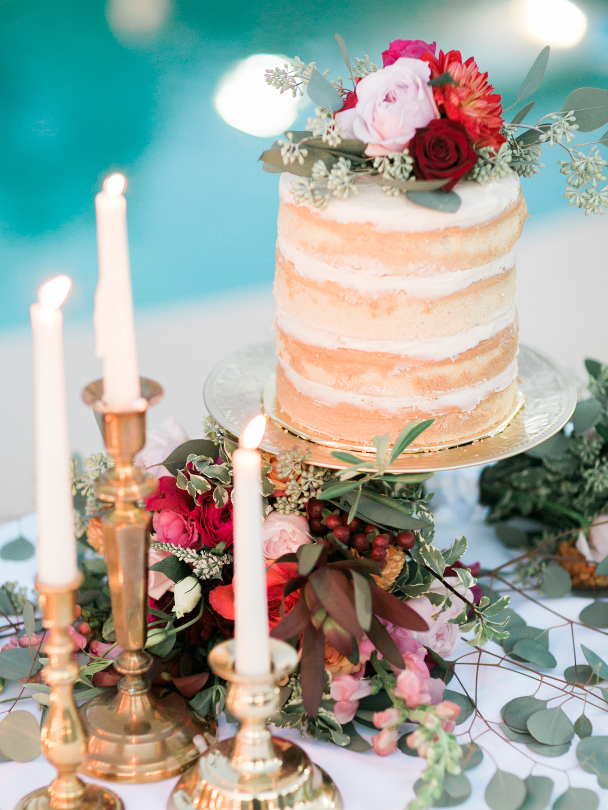 Gorgeous naked cake adorned with florals, surrounded by brass candlesticks