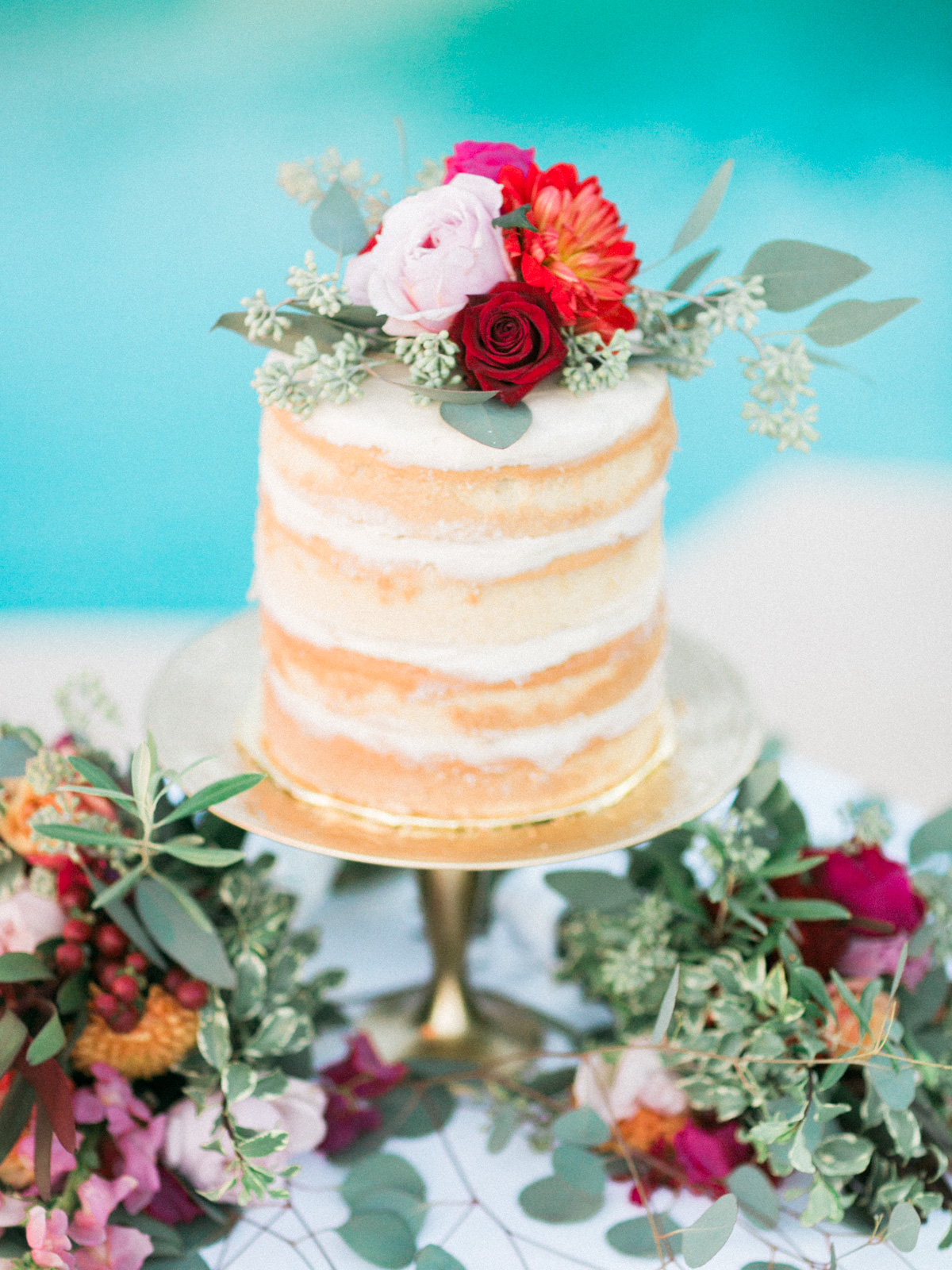 Simple and sweet naked cake surrounded by greenery and florals