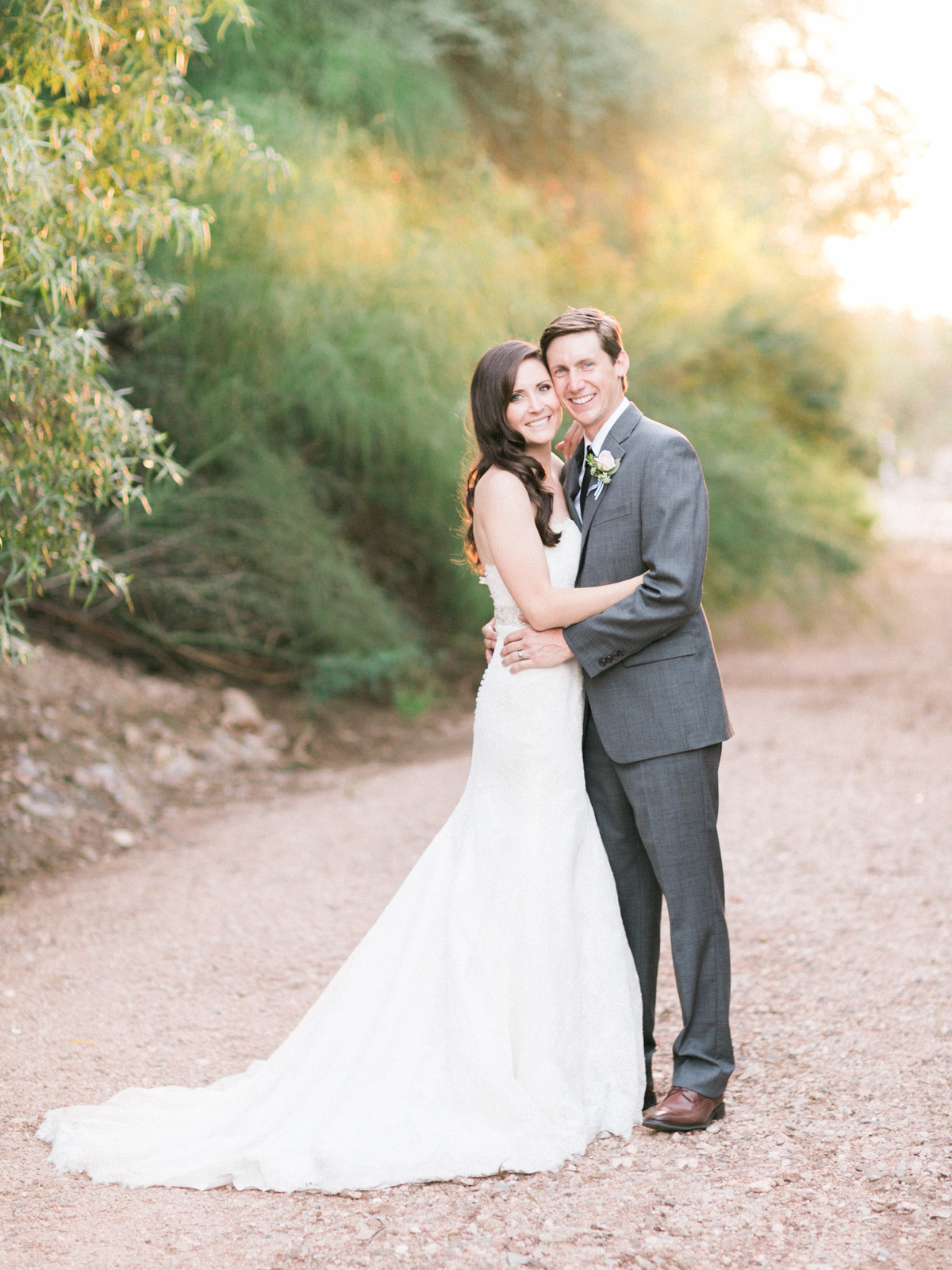 Gorgeous bride and groom smiling with gorgeous golden light captured by Phoenix wedding photographers, Betsy & John