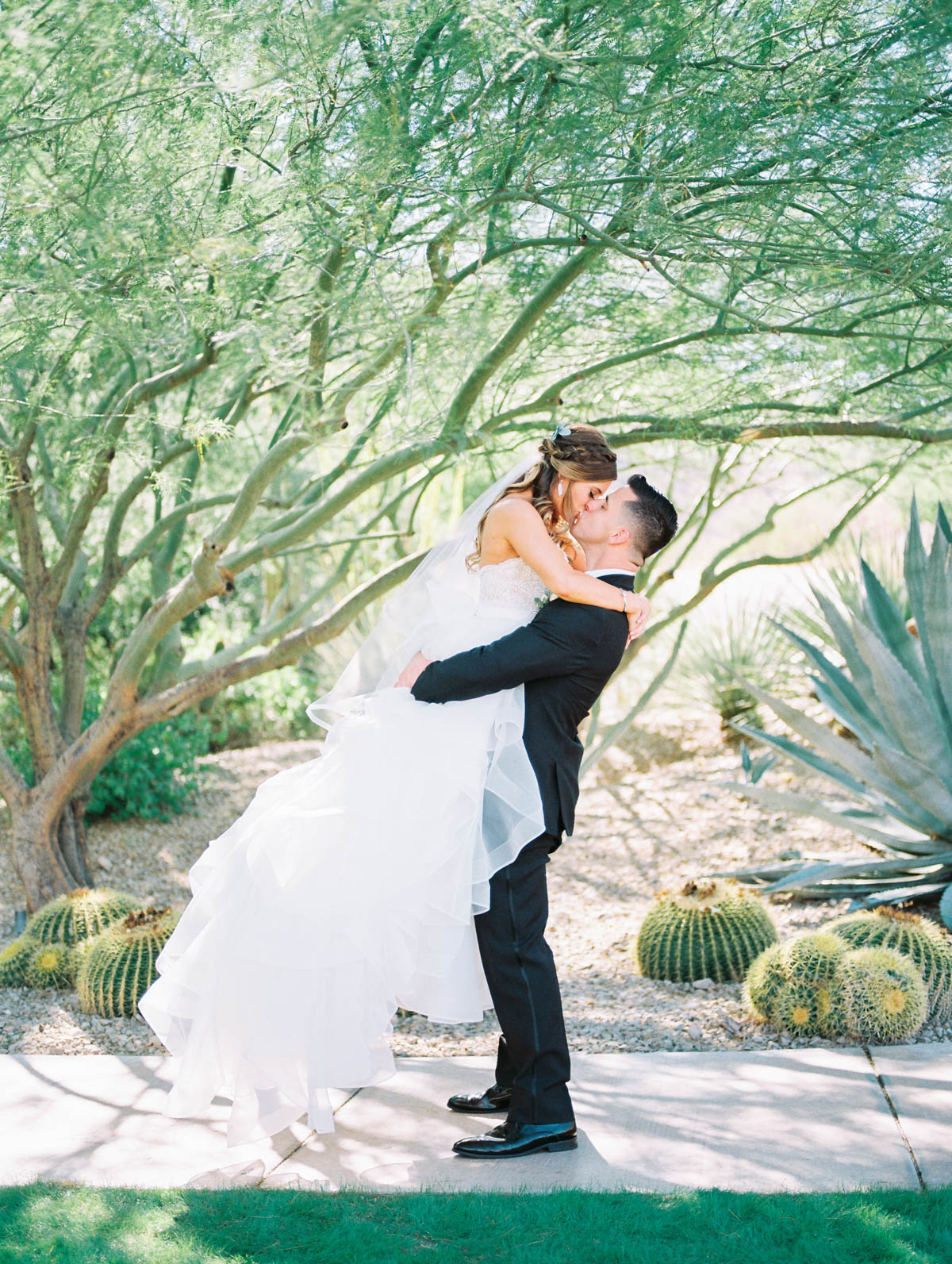 Groom picking up bride kissing captured by Tucson Wedding Photographers Betsy & John