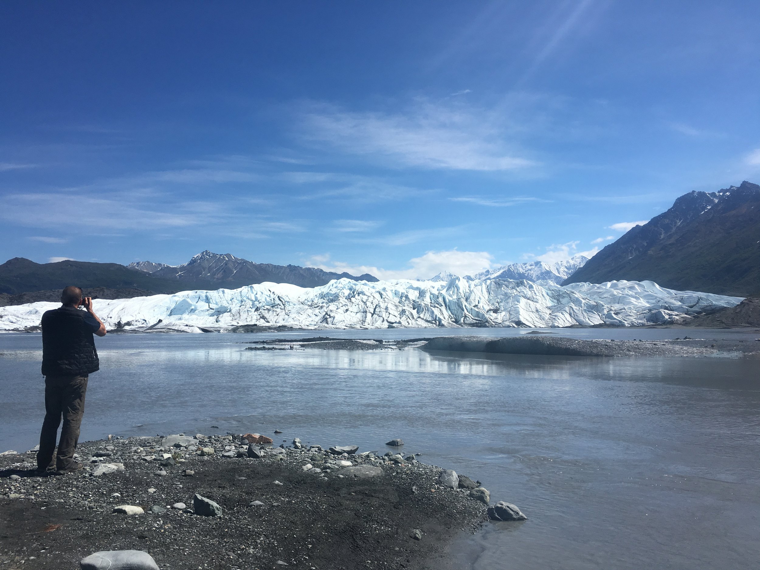 Benji taking photos of the edge of Matanuska glacier from across the water, near the parking area.