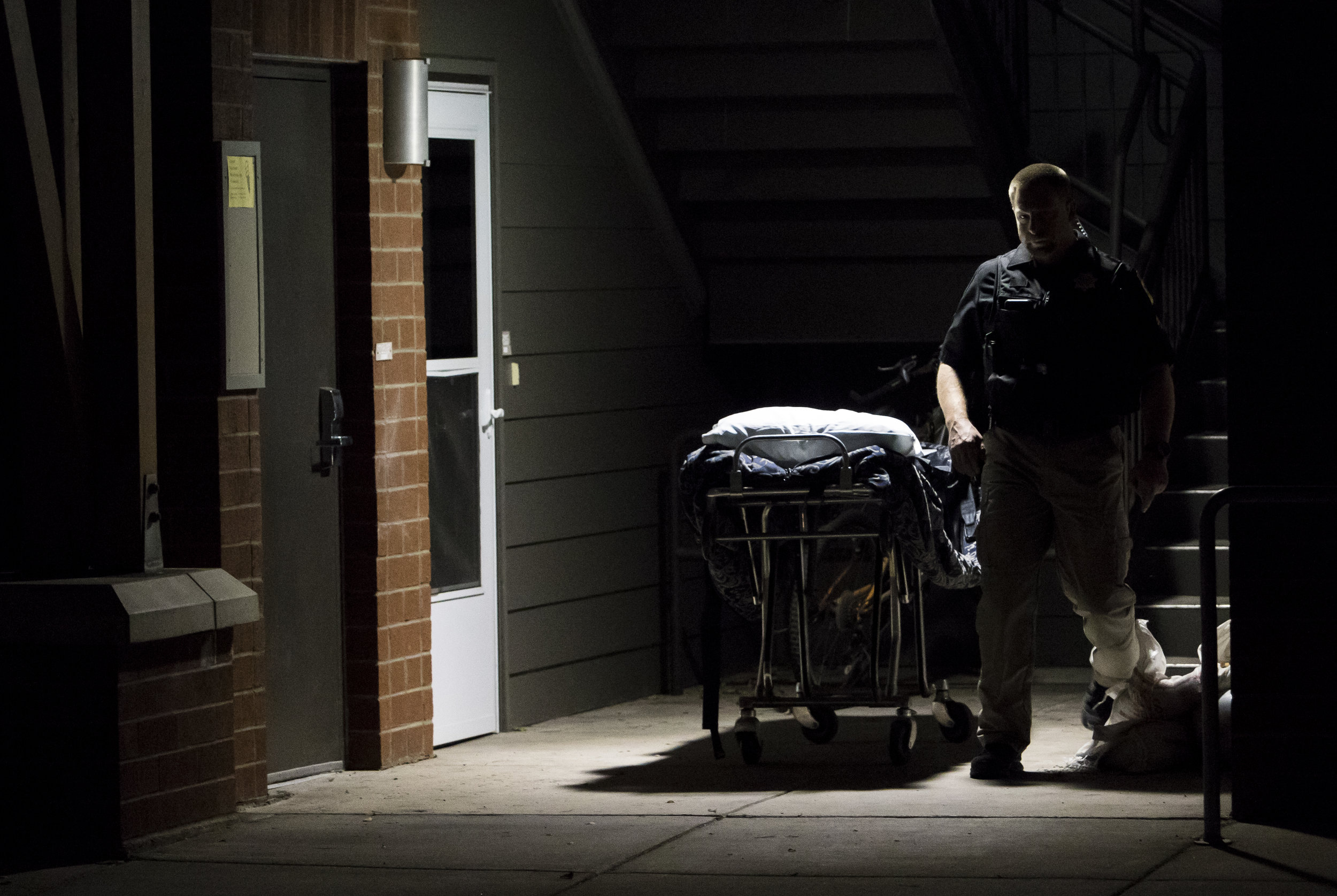 A police officer walks by an empty gurney on the first floor of building H in the Lewis and Clark Villages in Missoula, Mont. on Sept. 17, 2016. Police were called to the scene at 5:15 p.m. after a student's body was found. (Lacey Young, Montana Kaimin)