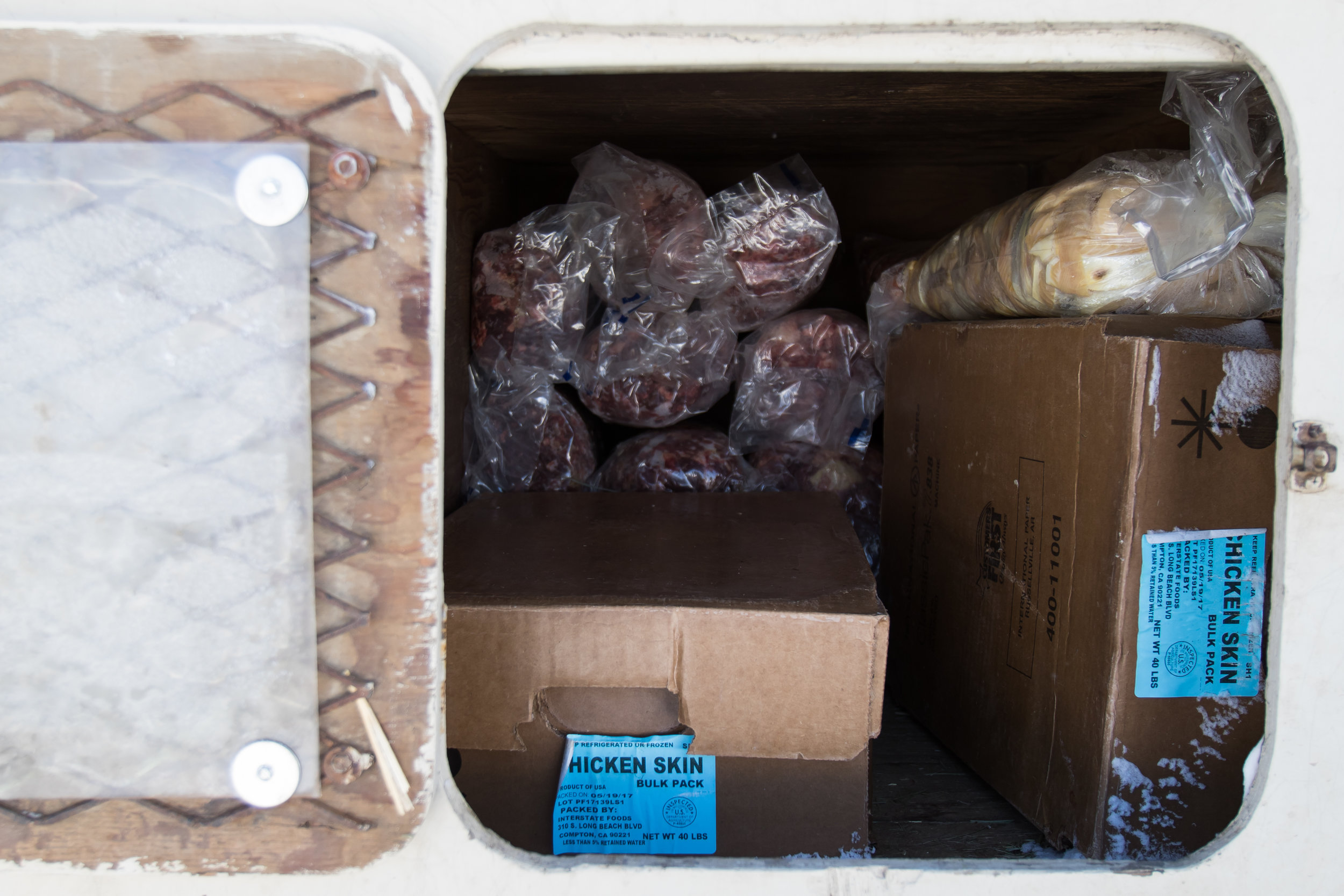 """A variety of chicken skins sit in a cubby of first-time musher Tyler Olson's dog trailer. Olson plans to bring 8 pounds of chicken skins on his 100-mile race as """"maintenance food"""" for his dogs."""