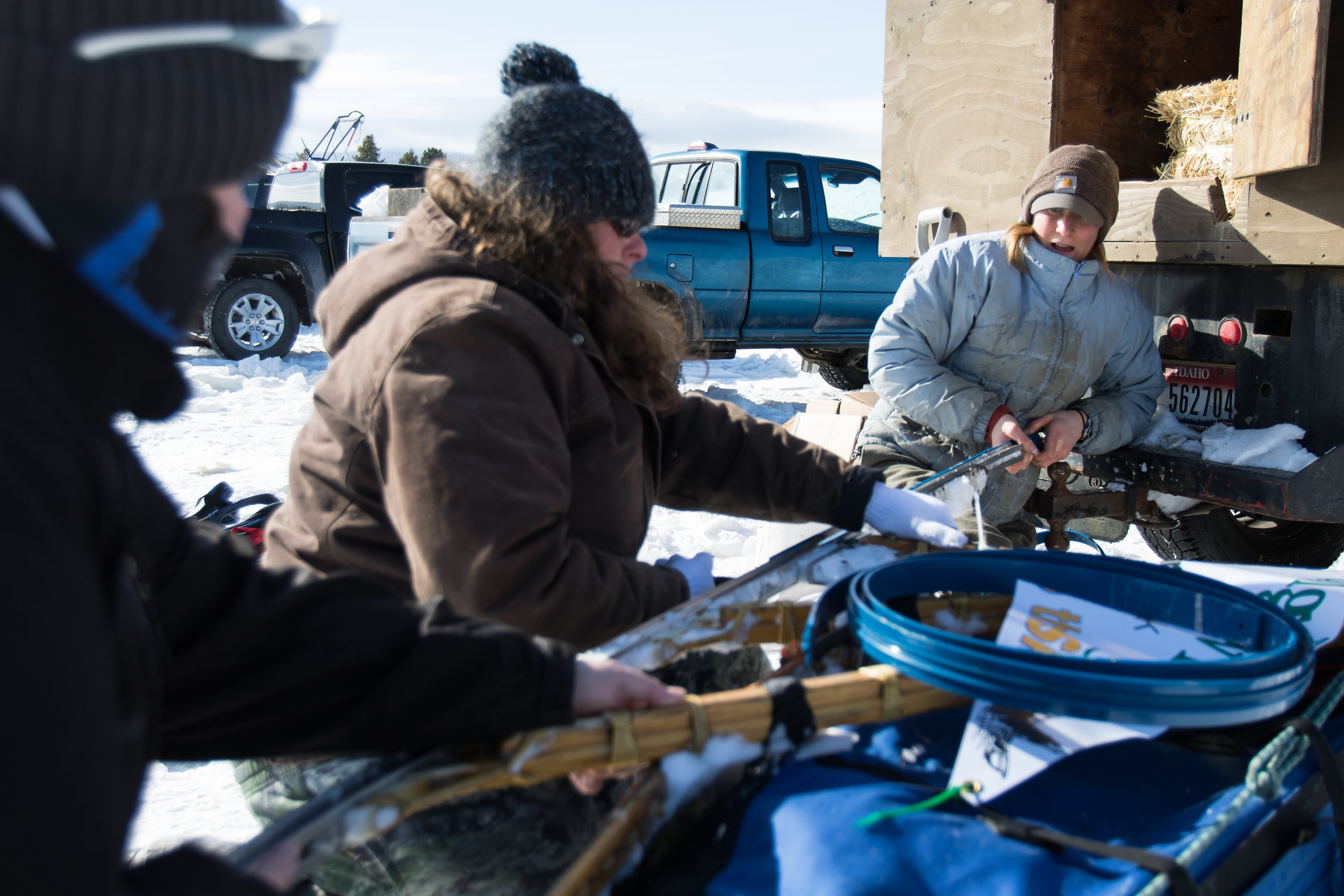 "Musher Josi Thyr's ""pit crew"" helps her change a runner on her dog sled. The blue runners are used for races in 8 to -16 degree weather."
