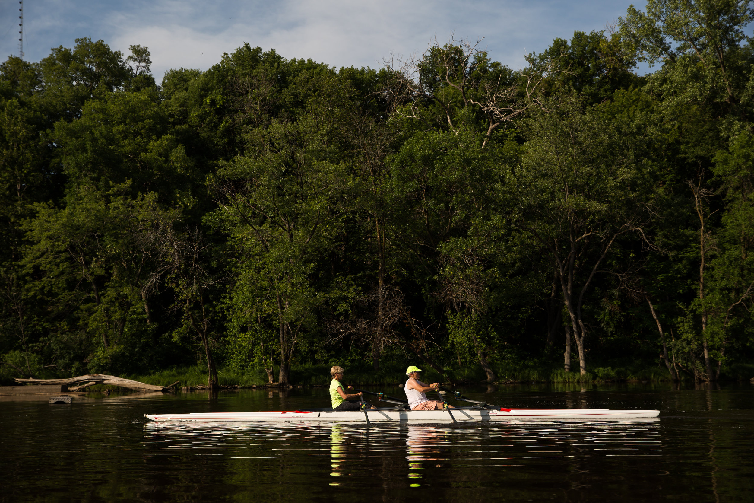 Joy Rikala, left, and Judy Winiecki row a two-person shell up the Mississippi River during a two-hour practice in Minneapolis, Minn. on July 13, 2018. (Lacey Young, MPR News)