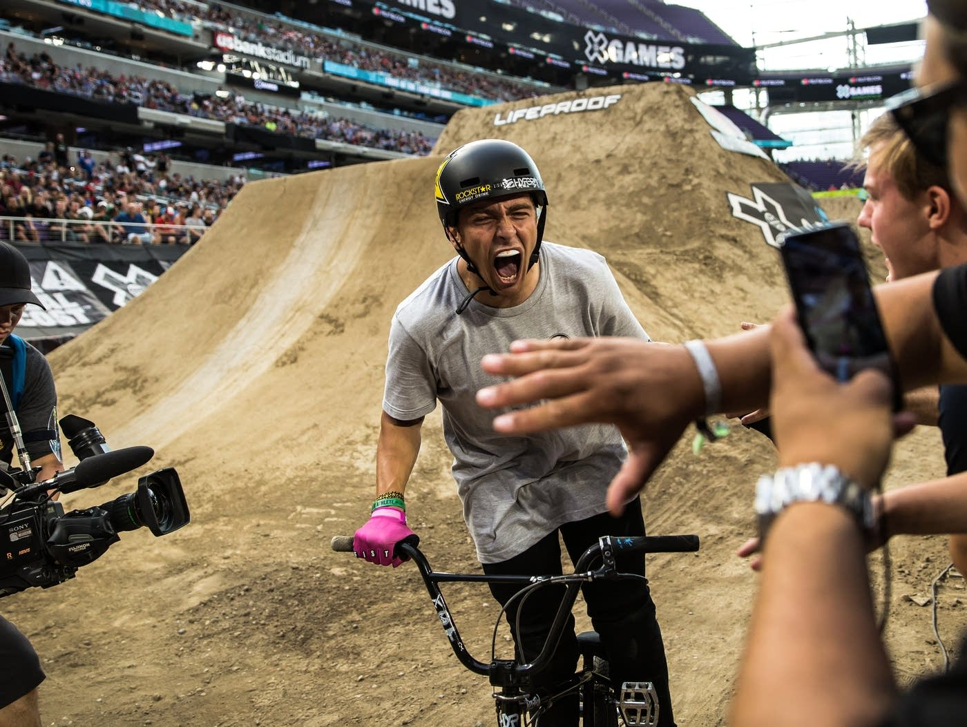 BMX rider Brandon Loupos celebrates after taking the lead in the BMX dirt final during X Games Minneapolis in U.S. Bank Stadium on July 21, 2018. Of three runs, Loupos' best score was 95 out of 100, and he finished in first place. (Lacey Young, MPR News)
