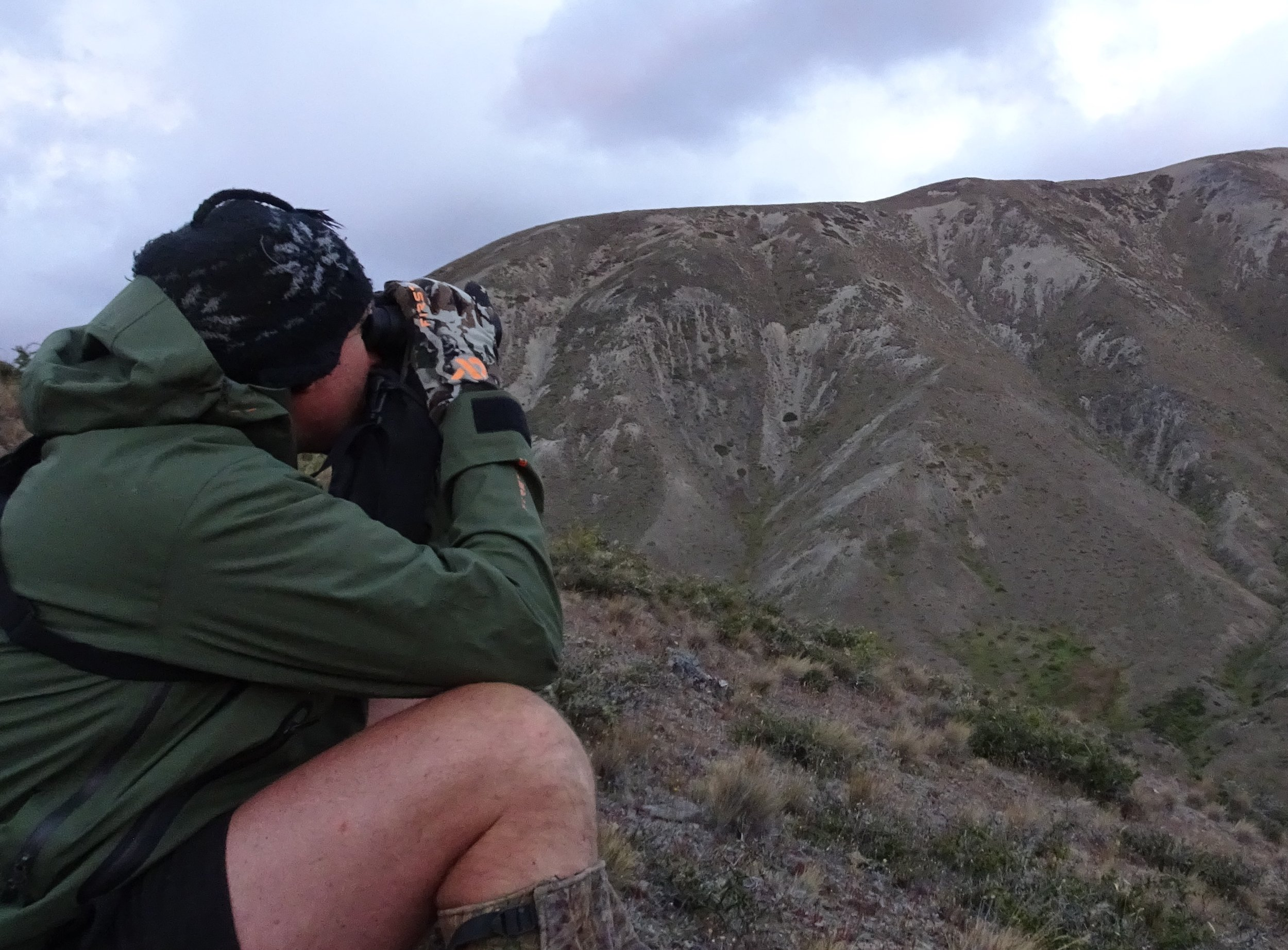 Shaun Monk sitting in the strong wind to spot into the sheltered gully heads, the First Lite merino gloves and the plain green  Seak Stormtight  packable jacket kept the showers and wind at bay. The jackets big under arm vents were great to zip open when climbing hard in the heat.