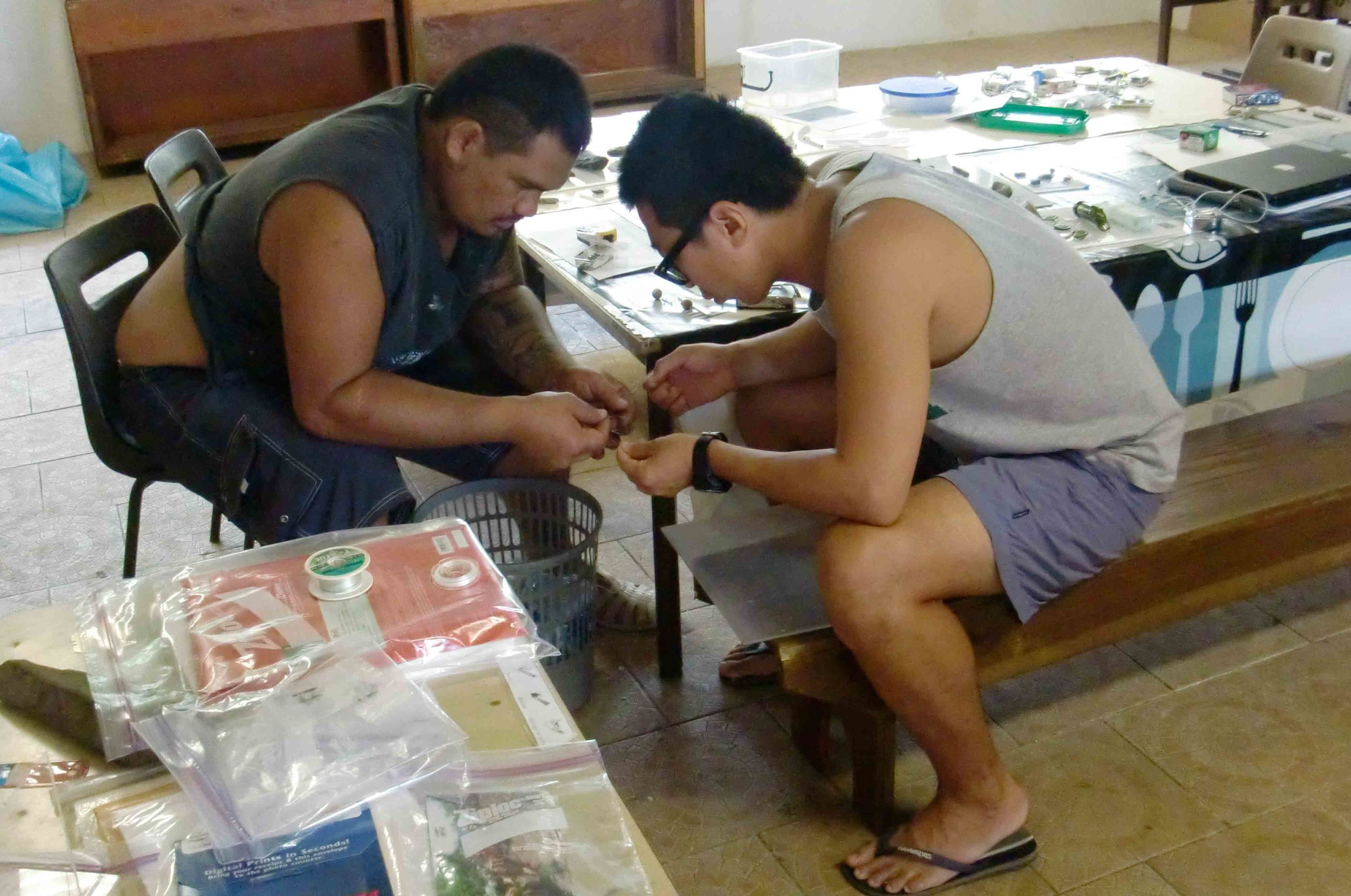 "2013. Mounting fishhooks for the ""Treasures of Tahuata"" exhibit. In action: Joseph Barsinas and Shingo Suzuki."