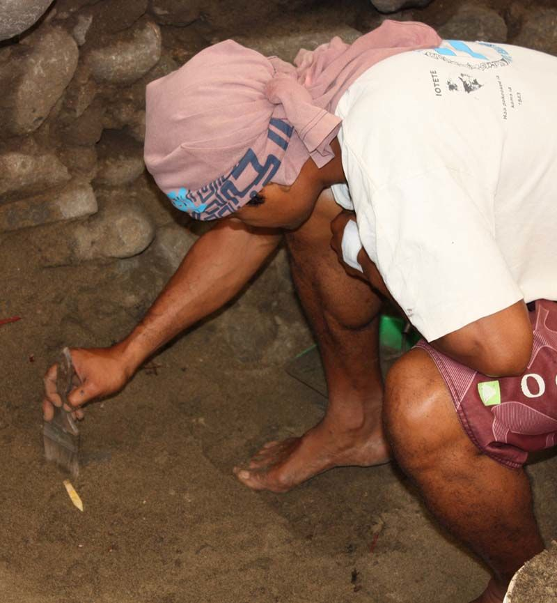 Samuel Tiaiho uncovering a 700 year old pearl shell lure shank found more than two meters below the ground surface.