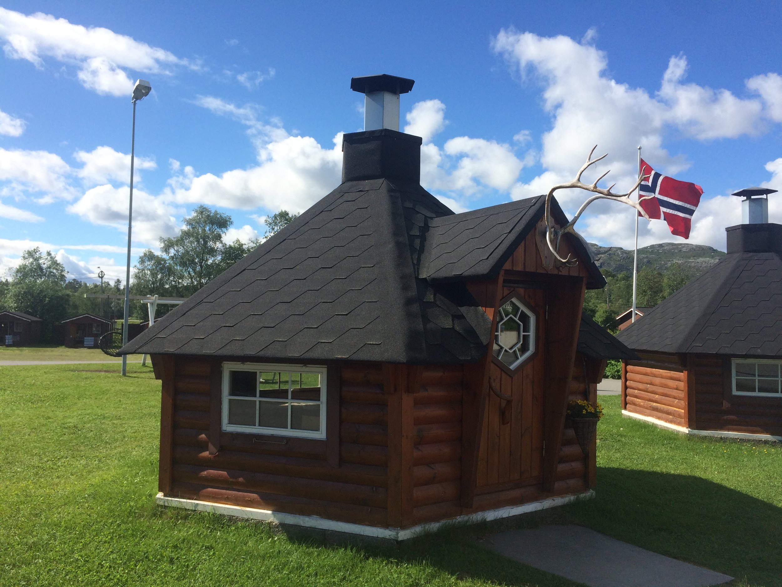 Typical Norway - A barbeque hut with a fire pit in the middle with benches around for some outdoor cooking in the warm.