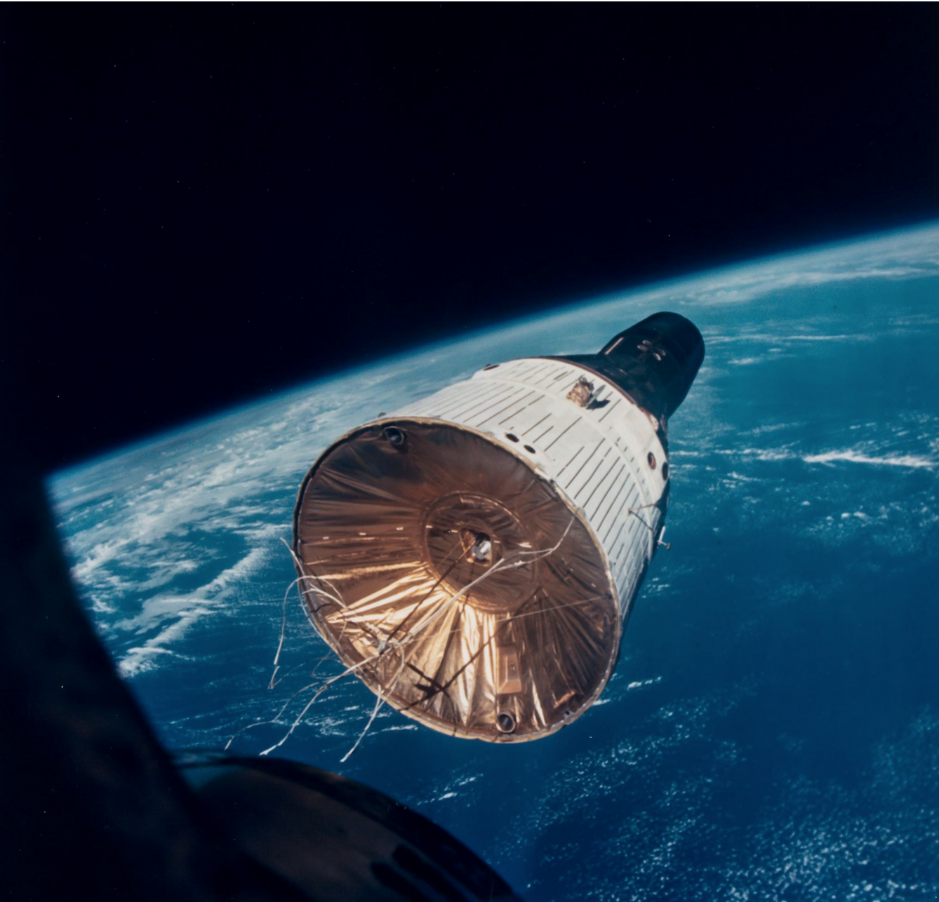 Gemini 7 as seen from Gemini 6. Note gold mylar thermal blanket over aft end of spacecraft. (Photo credit: NASA.)