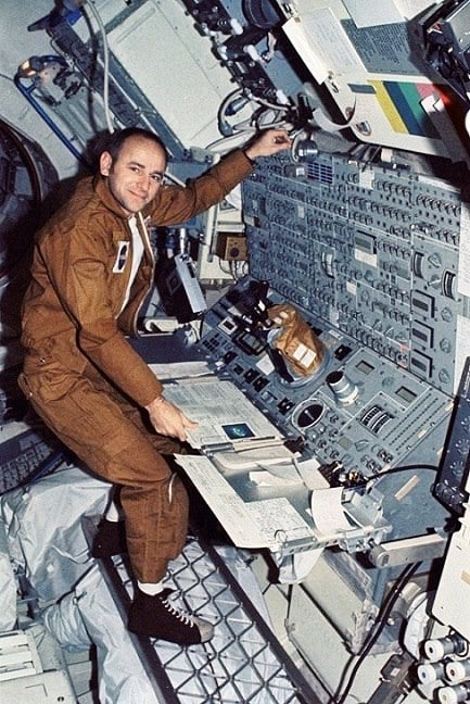 Compare the right-hand figure in painting 22 with Skylab astronaut Alan Bean in the weightless neutral body posture with cleat-in-grid foot restraint at the solar telescope console (NASA photo S74-5150).