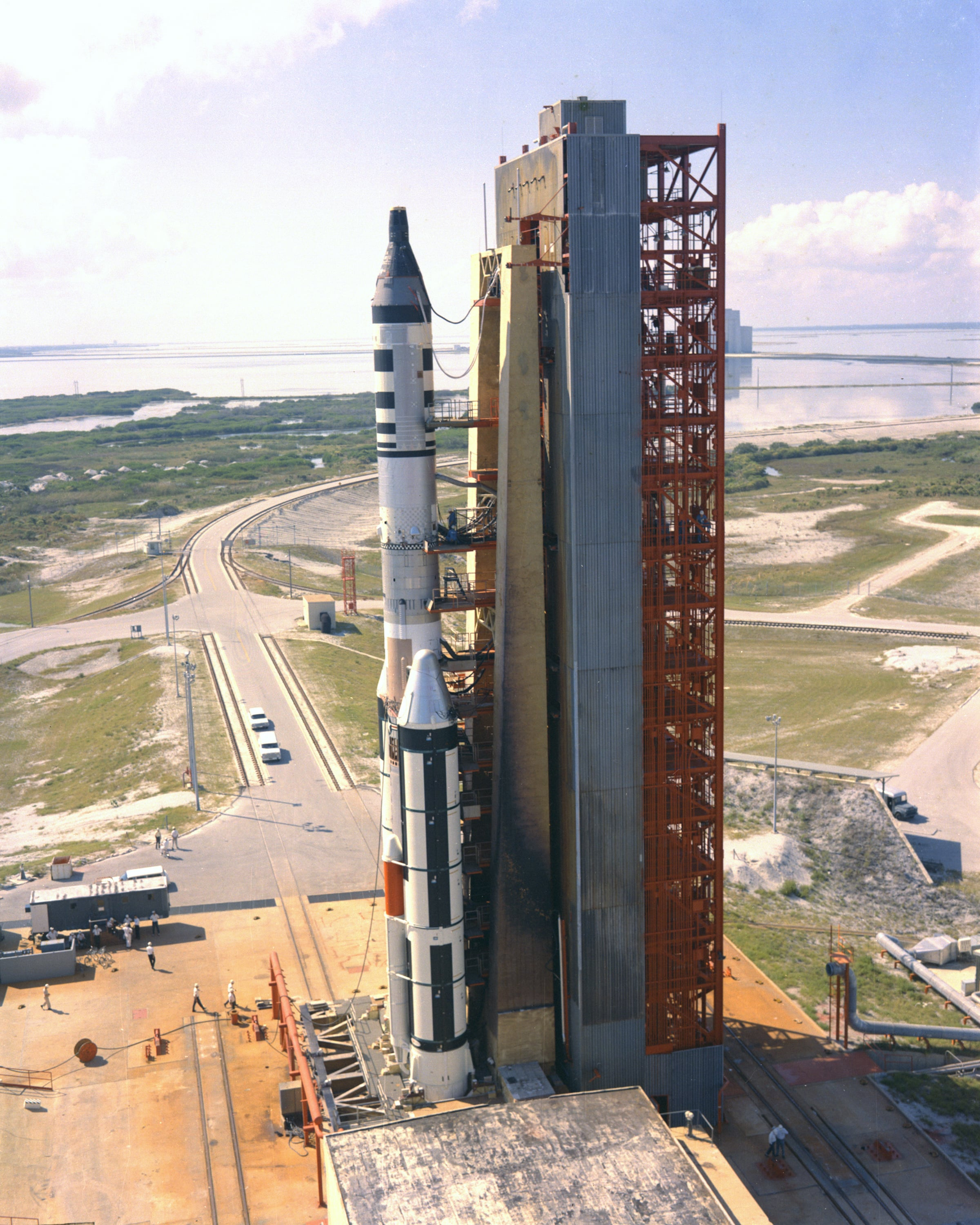 Titan IIIC number 9 is shown at Space Launch Complex 40 at Cape Canaveral Air Force Station. It was launched on November 3, 1966, as a test of the rocket. It also carried the Gemini 2 spacecraft, on its second suborbital flight to evaluate its heat shield as modified for MOL, and a simulated MOL canister carrying Air Force experiments. Note the similarity of the its umbilical tower to that in Painting #7. (Photo PL66C-76206, USAF)