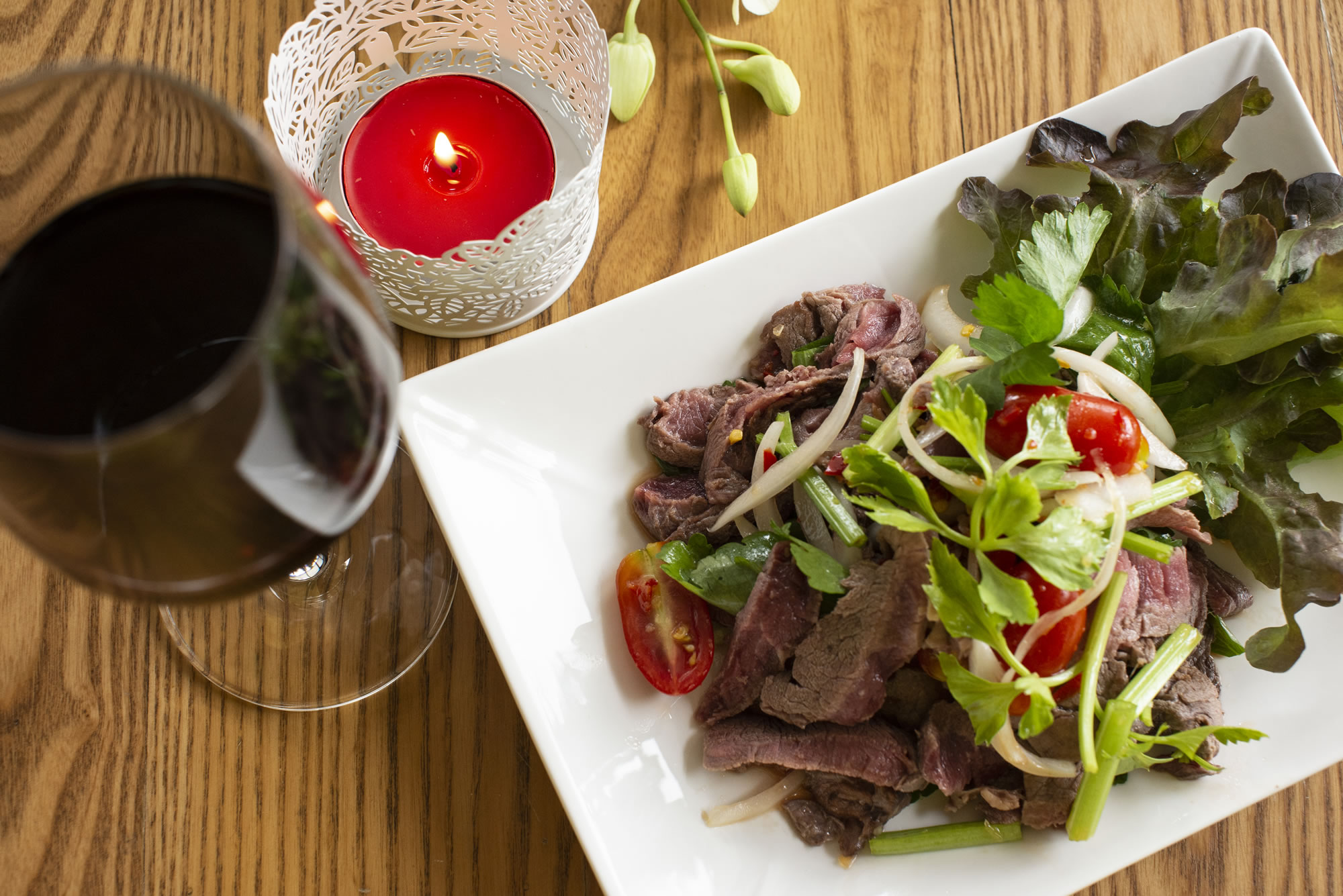 YUM NEUA - BEEF SALAD -  Thinly sliced grilled beef seasoned with chillies, chopped onions and lemon juice.