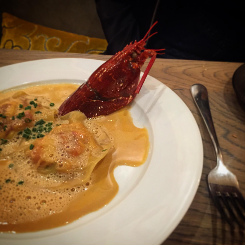 Signature lobster ravioli with leek and shellfish sauce