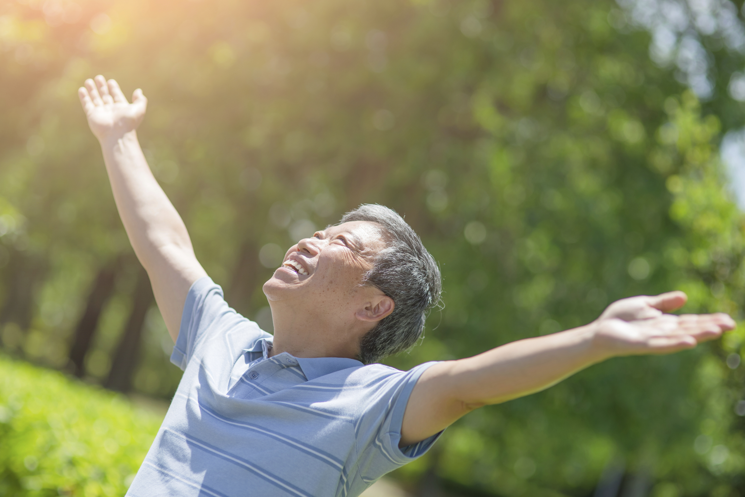 Man with raised arms, smiling, looking up at sky.