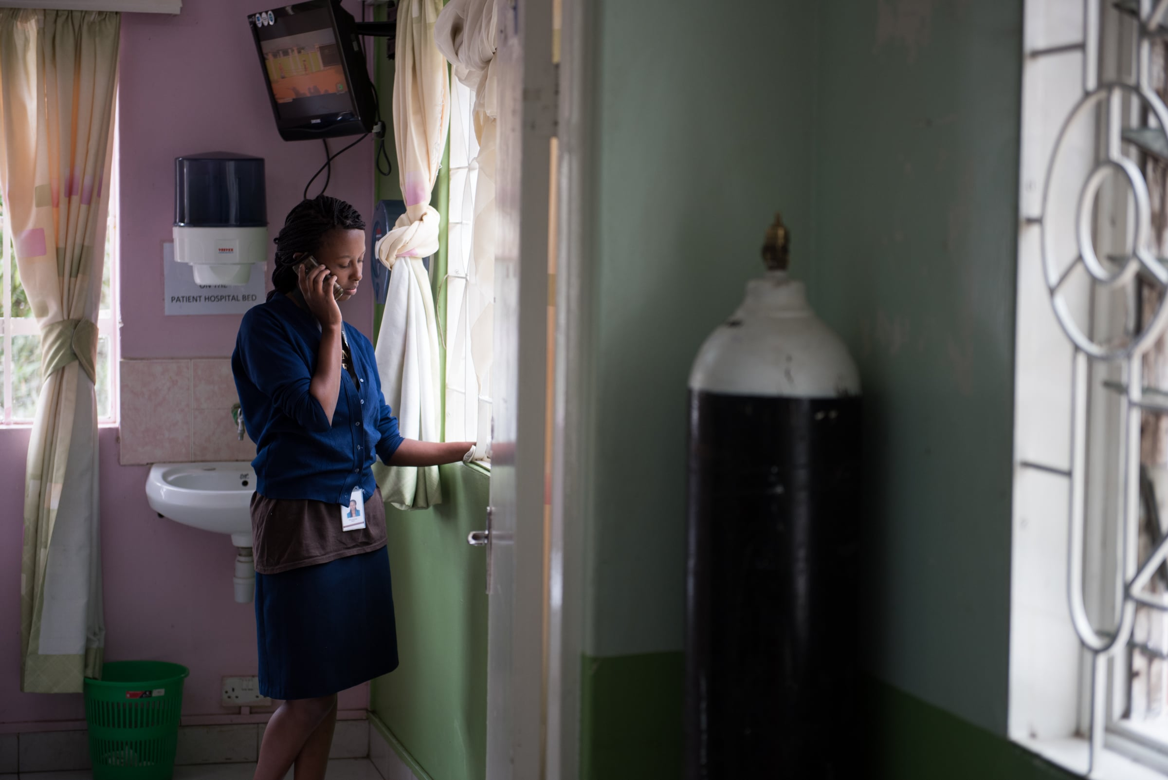 Nurse Milca Mwankiki talks on the phone with a friend during a break in her shift. For nurses like Milca who confront death regularly, connecting with friends and colleagues is an essential part of managing the stress of working in palliative care.