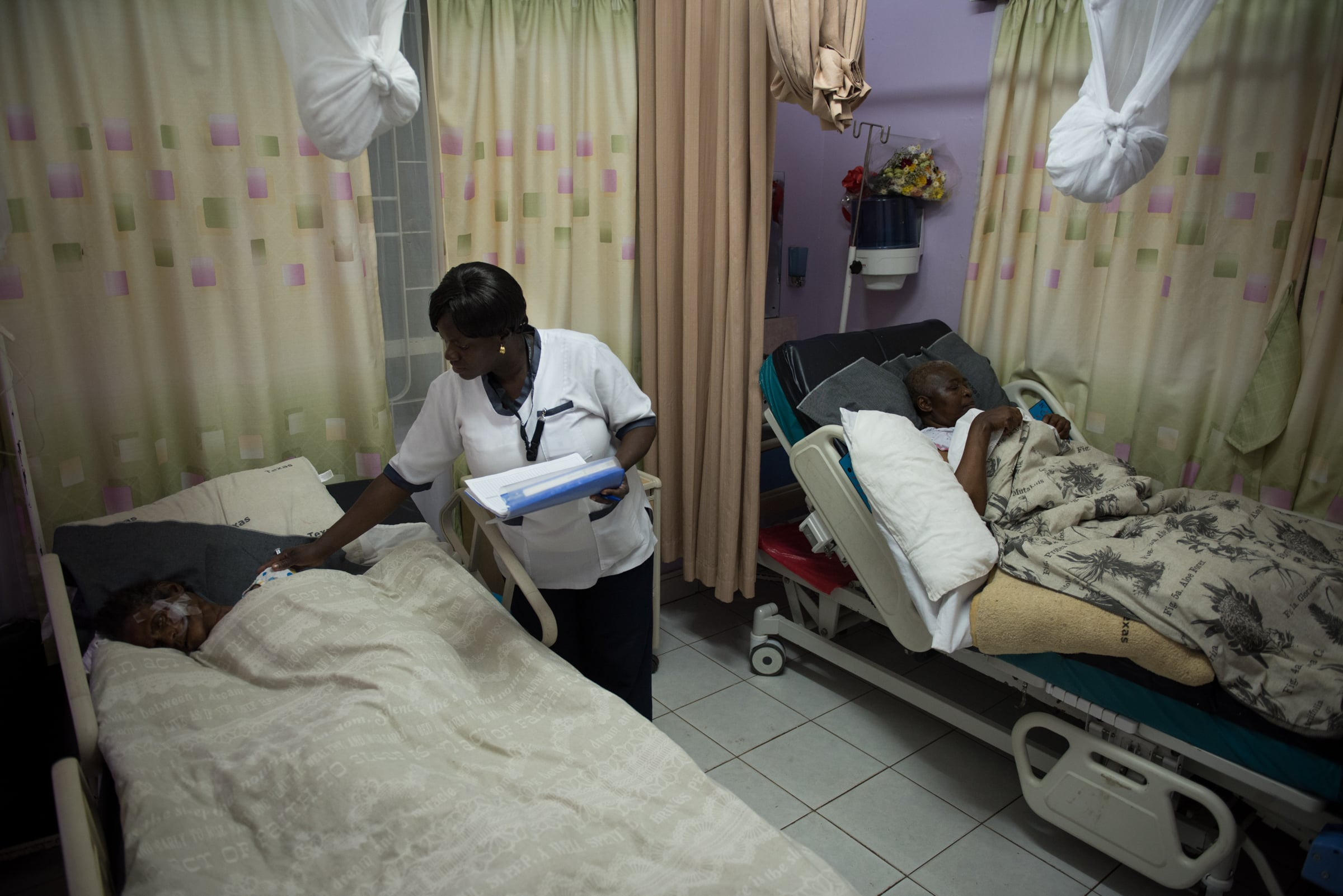 Nurse Carren Asembo checks on two patients at the Texas Cancer Center during the night shift.