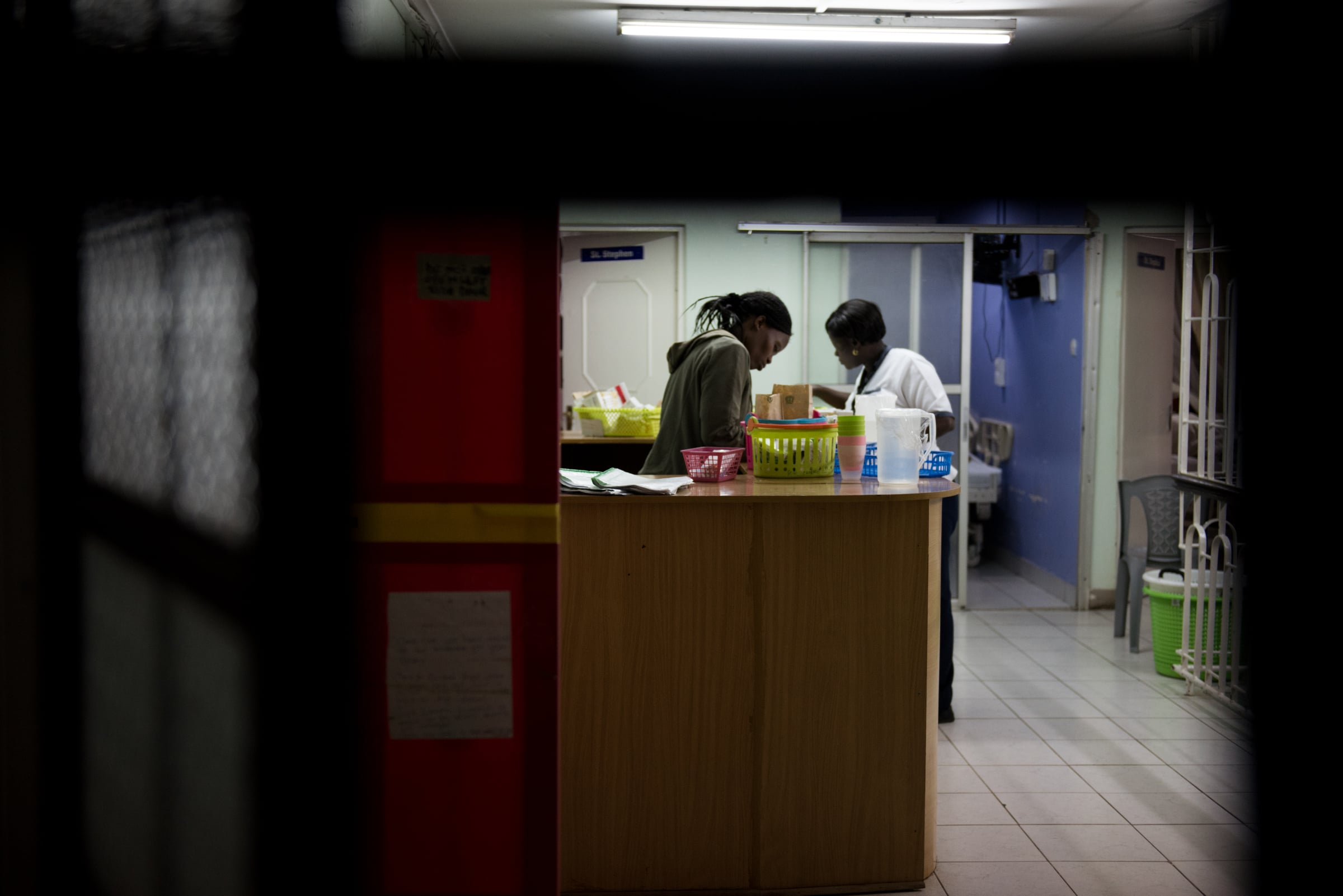 Nurse Rebecca Nandimaye, left, and Carren Asembo, prepare medications at the Nurses' Station during the night shift. Most medical professionals are not yet trained in palliative care. These nurses, who are legally barred from dispensing morphine and other opioids to patients in need, stand on the frontline of a national struggle with rising cancer diagnoses, HIV-related complications and other life-limiting illnesses.