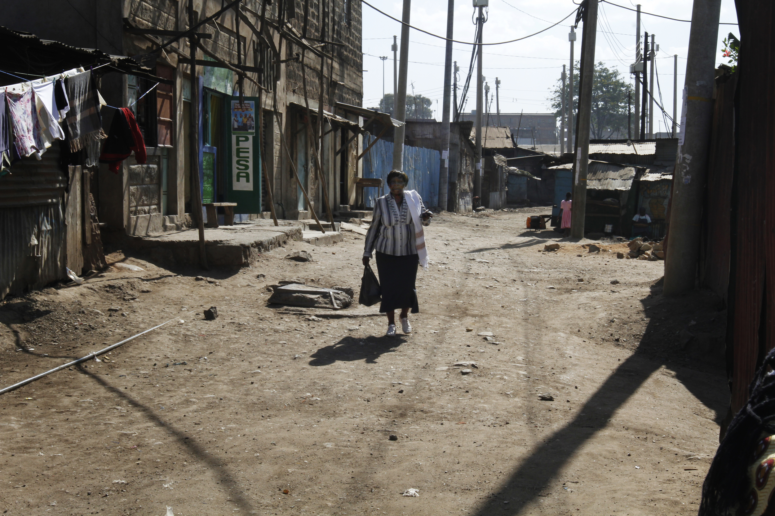 Rosemary Awuor who has breat cancer walks back to her home in Nairobis Mathare slum after a visit to the Hospital of 27th August 2015 copy.jpg