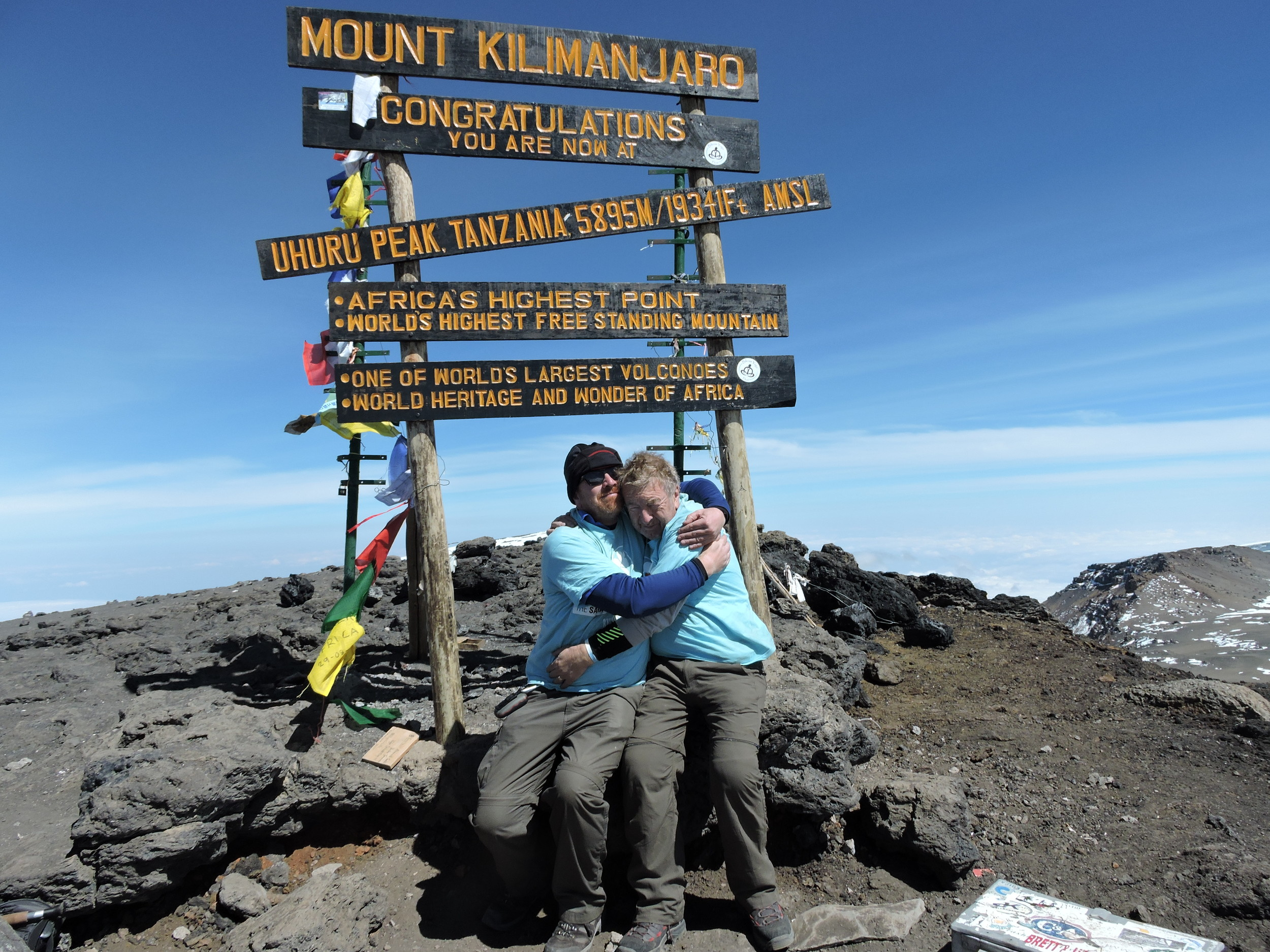 Sarah's father, Vic, and Sarah's half Brother, Simon, embrace at Uhuru Peak, the summit of Mount Kilimanjaro. A highly emotional occasion for them both.