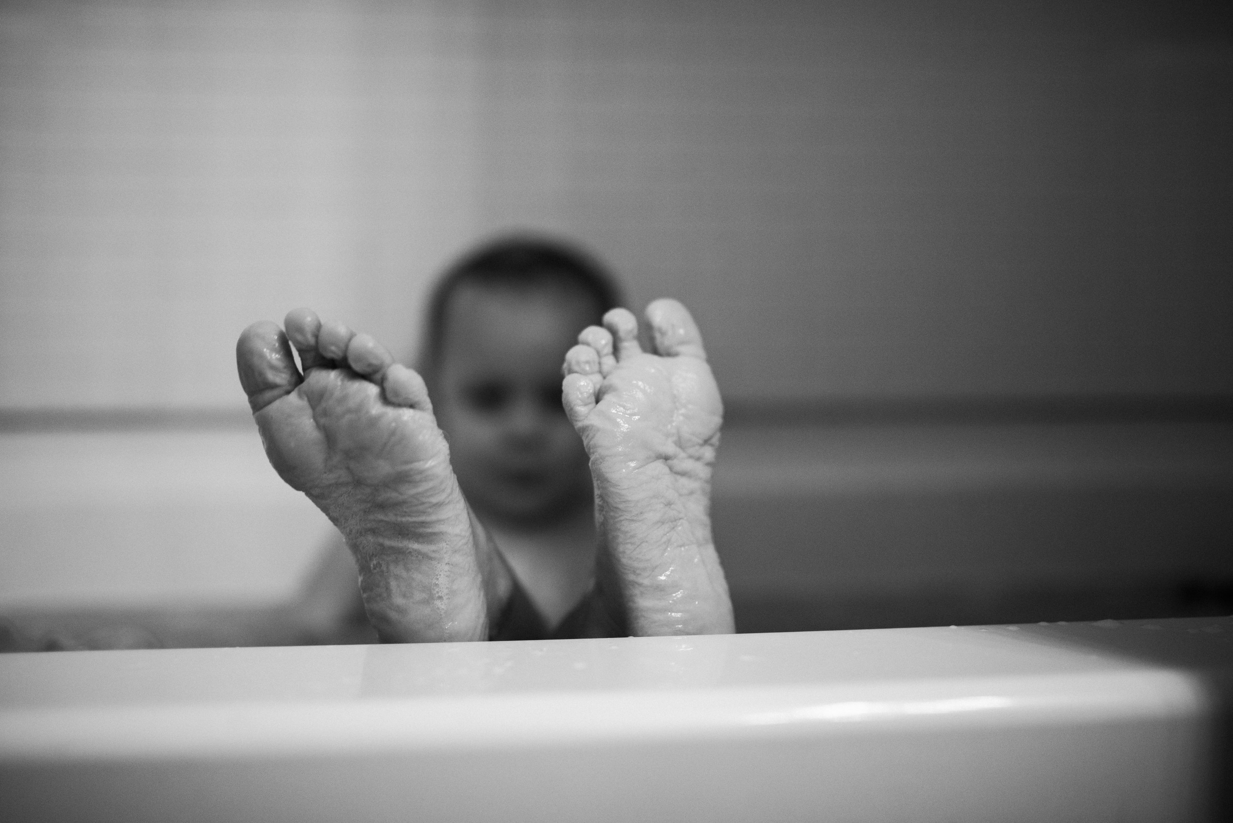 little boy with wrinkly piggies toes in the tub