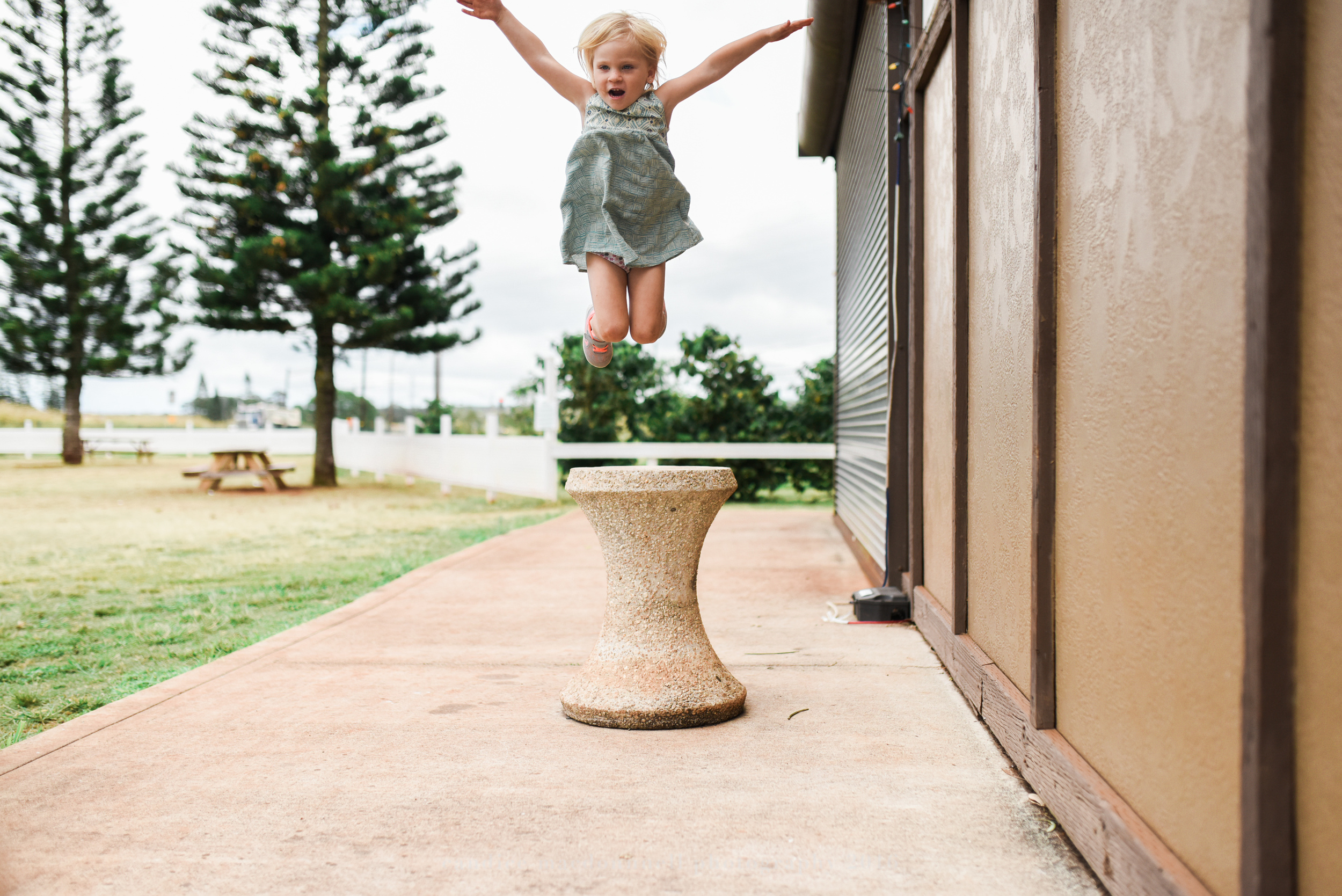girl jumping high at coffee farm documentary photograph oahu hawaii family lifestyle photographer
