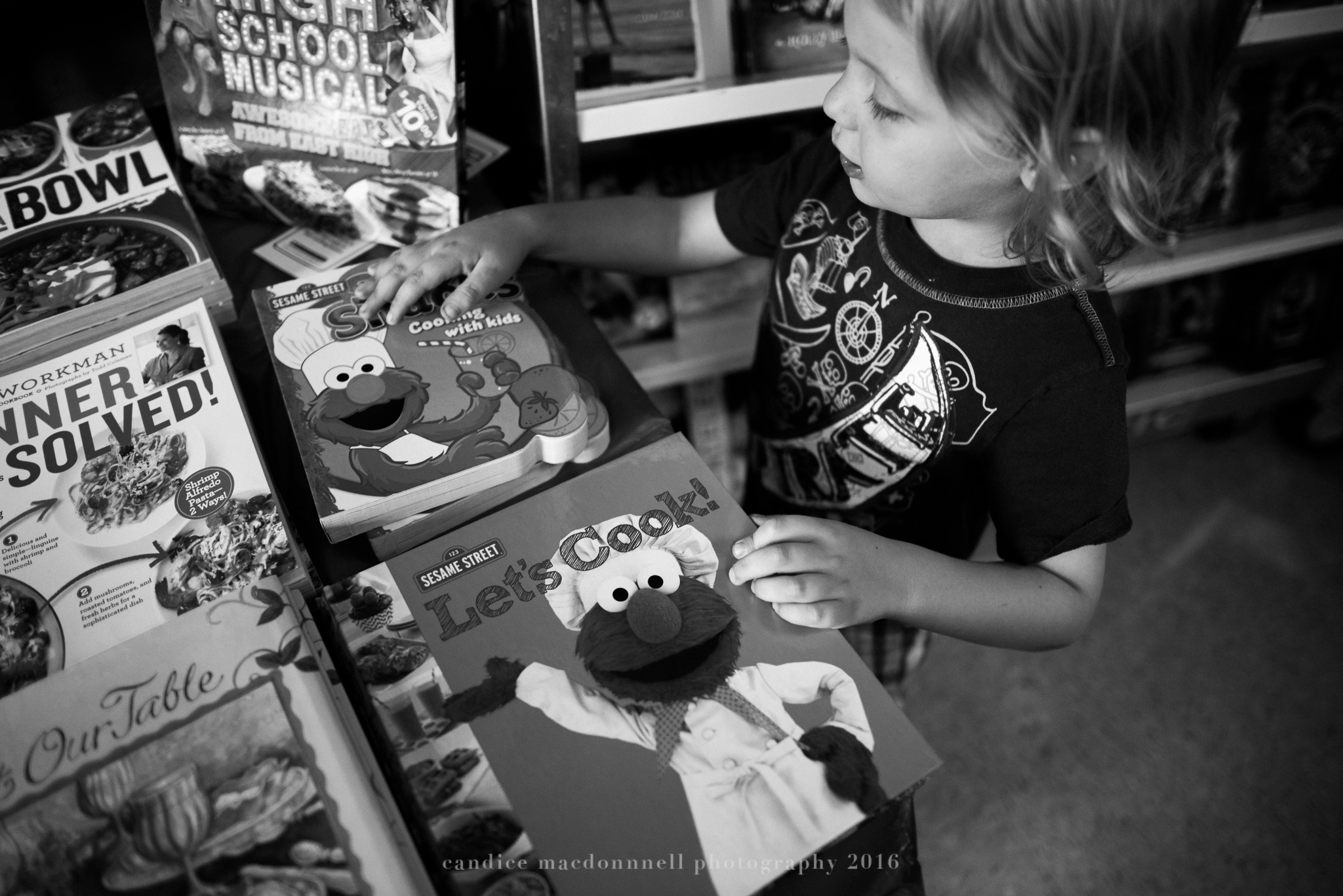 boy picking out books at bookfair oahu hawaii family lifestyle photographer