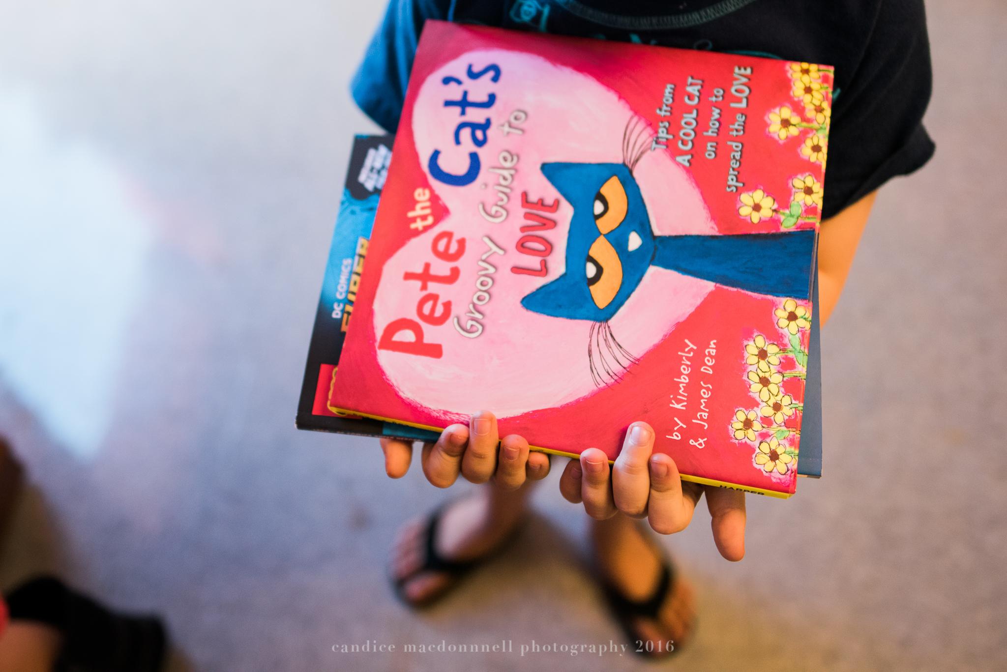 child holding book at bookfair oahu hawaii documentary family photographer