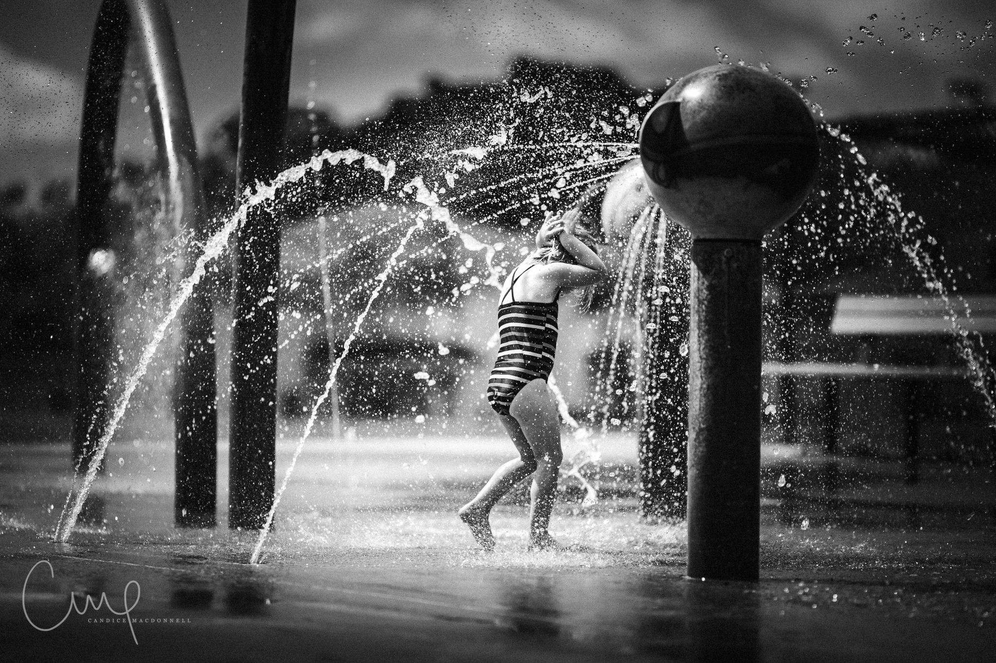 little girl playing in water at splash park hawaii family photography