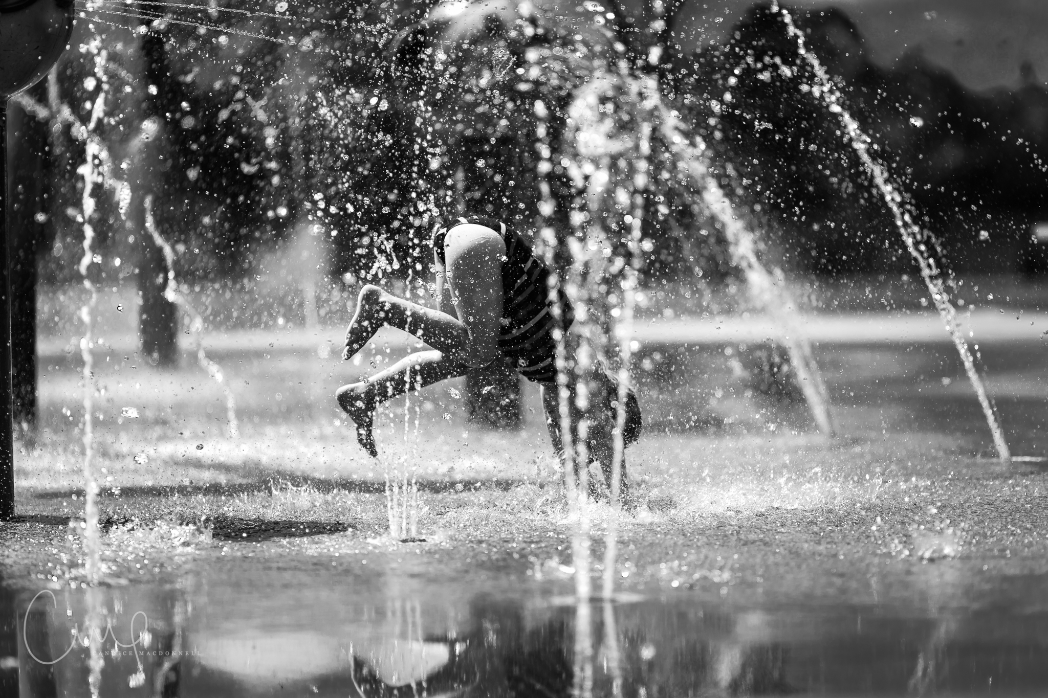 girl playing in water at splash park black and white oahu hawaii family documentary photogarphy