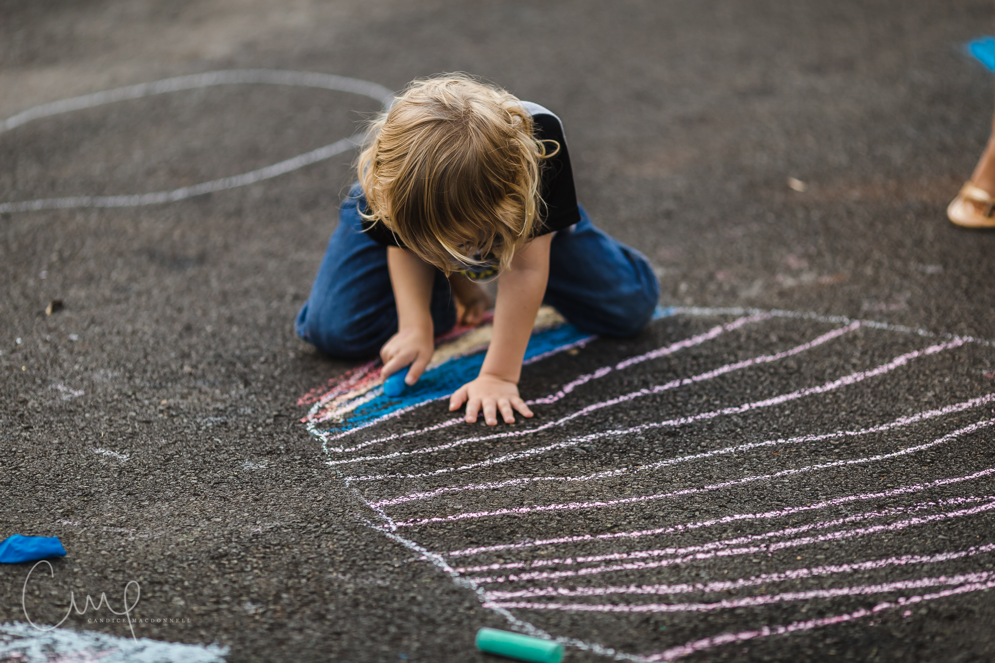 boy coloring with sidewalk chalk on road oahu hawaii lifestyle family photographer