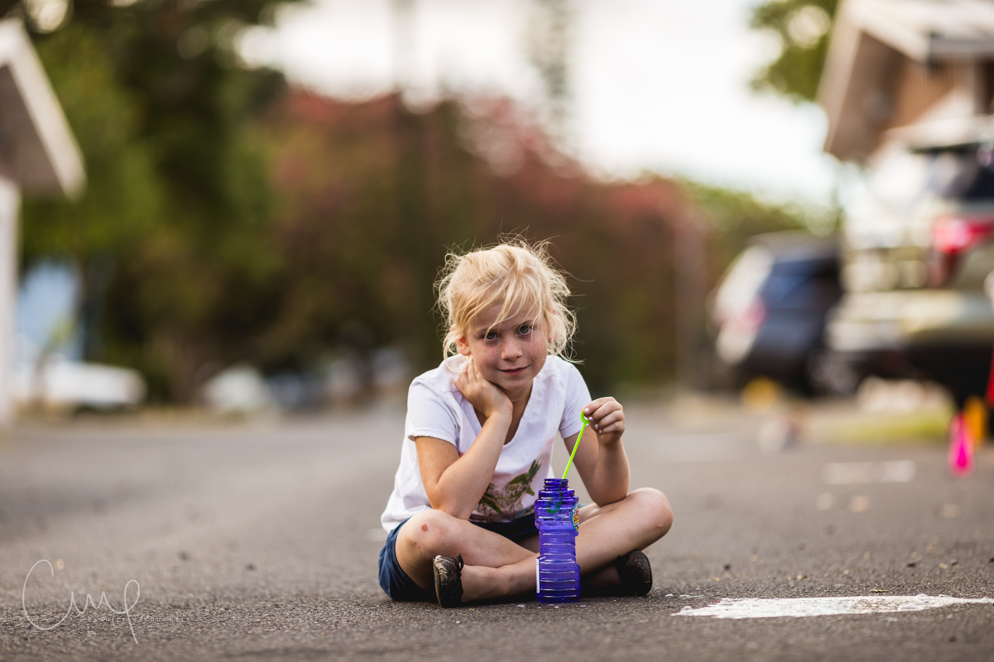 girl sitting and blowing bubbles in alley children's documentary photographer hawaii