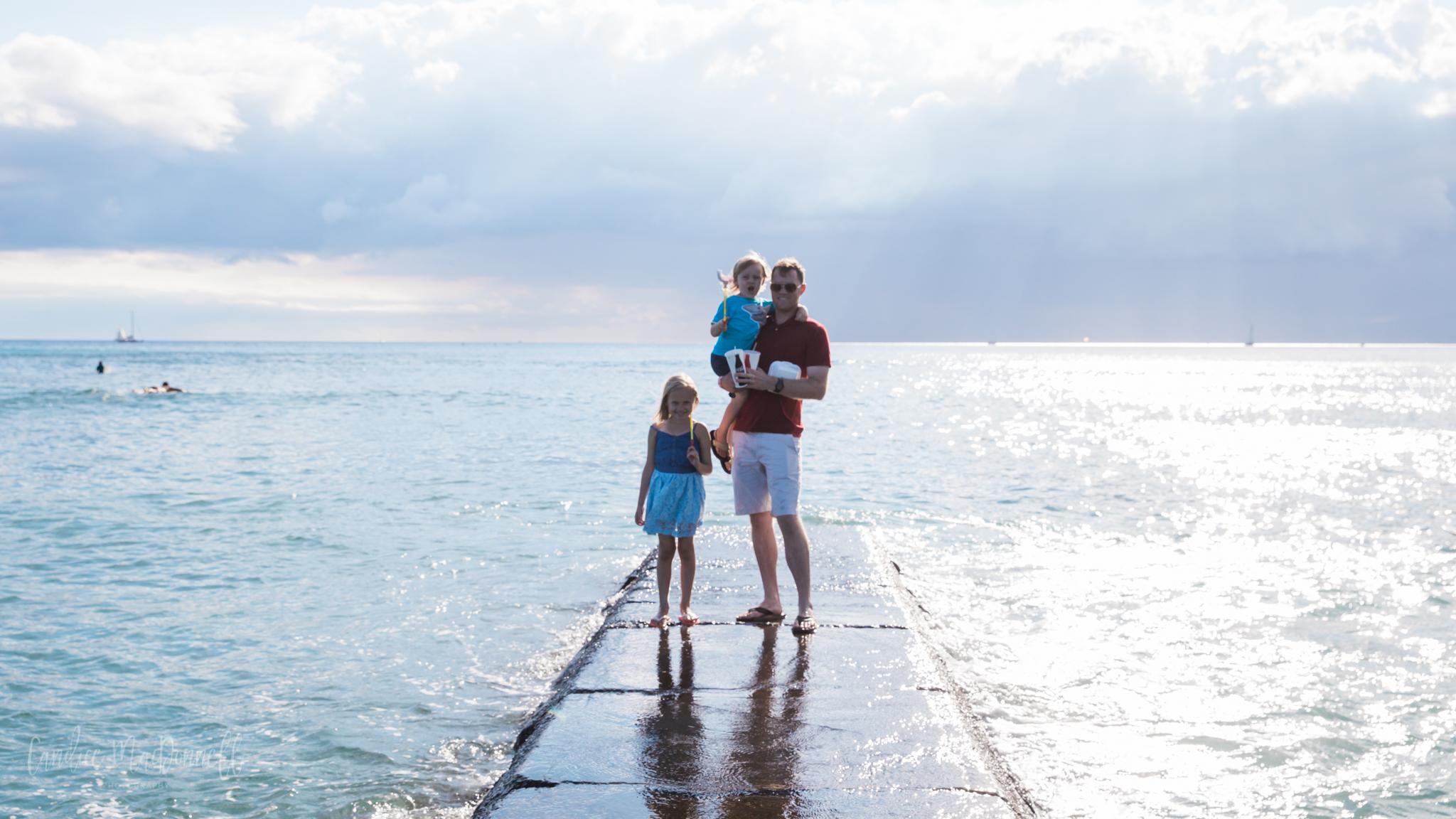 family on jetty pacific ocean honolulu hawaii