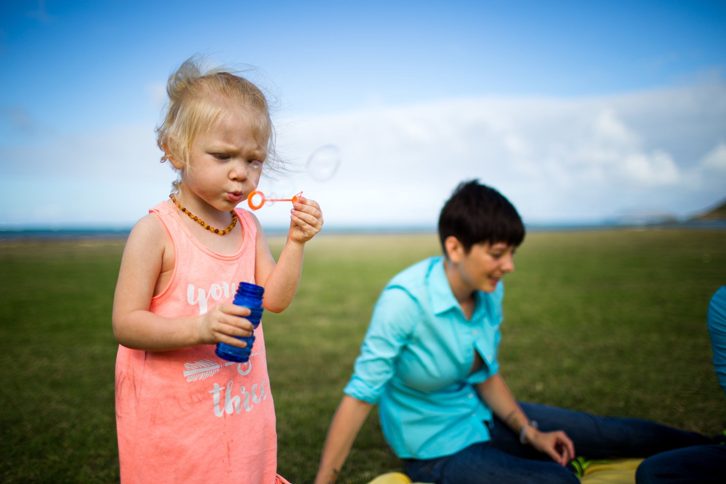 girl and mother blowing bubbles at park lifestyle documentary photography