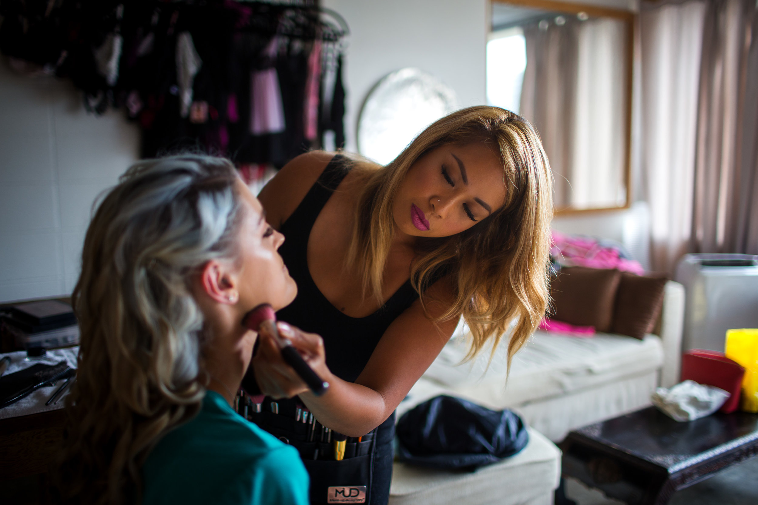 Woman getting hair and makeup done for bodouir photography session