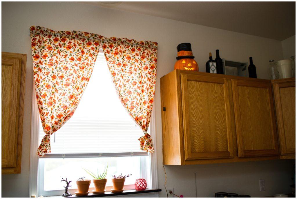 cute fall curtains and Halloween decorations on a custom made window ledge