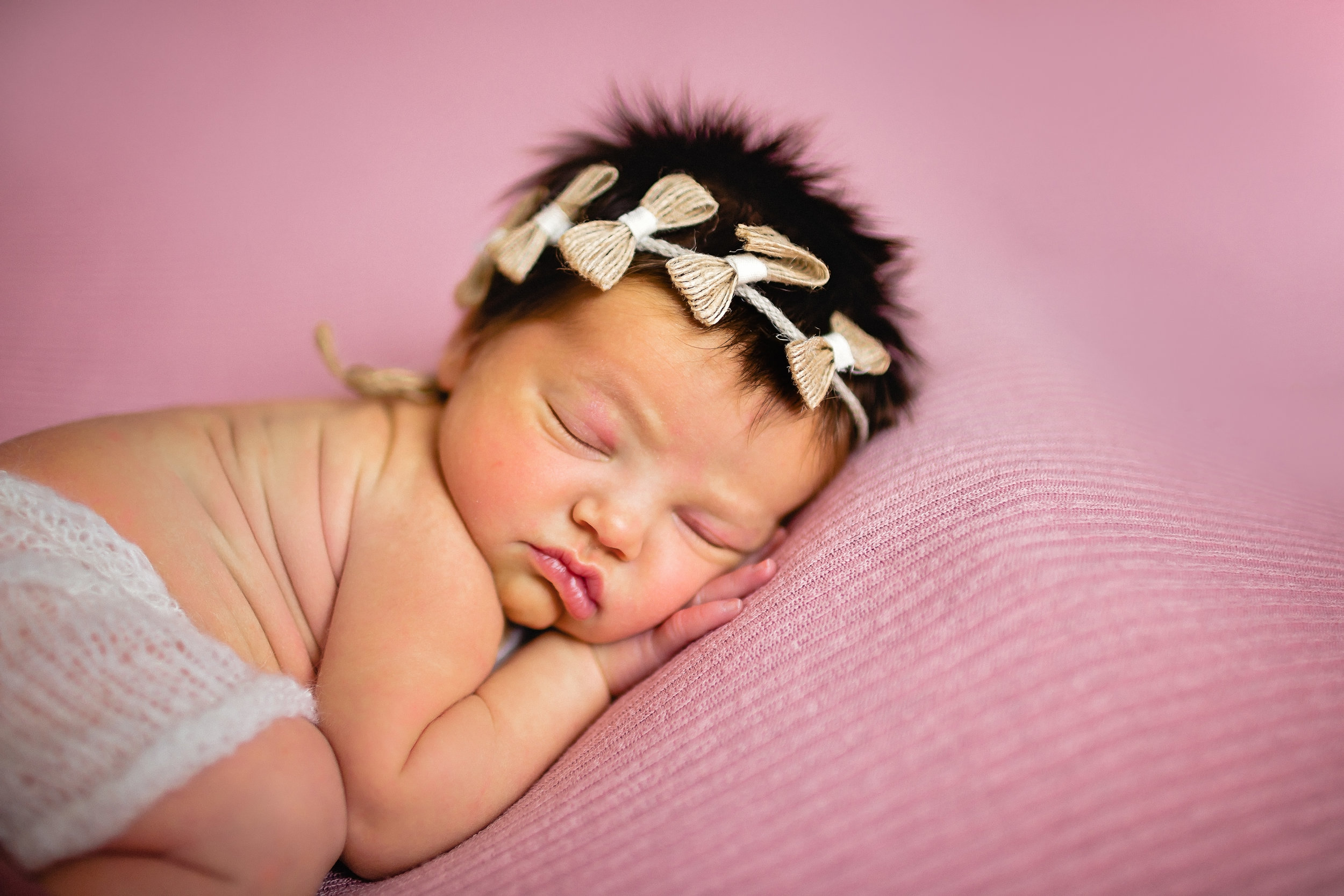 newborn photographer baby on pink blanket with lots of hair