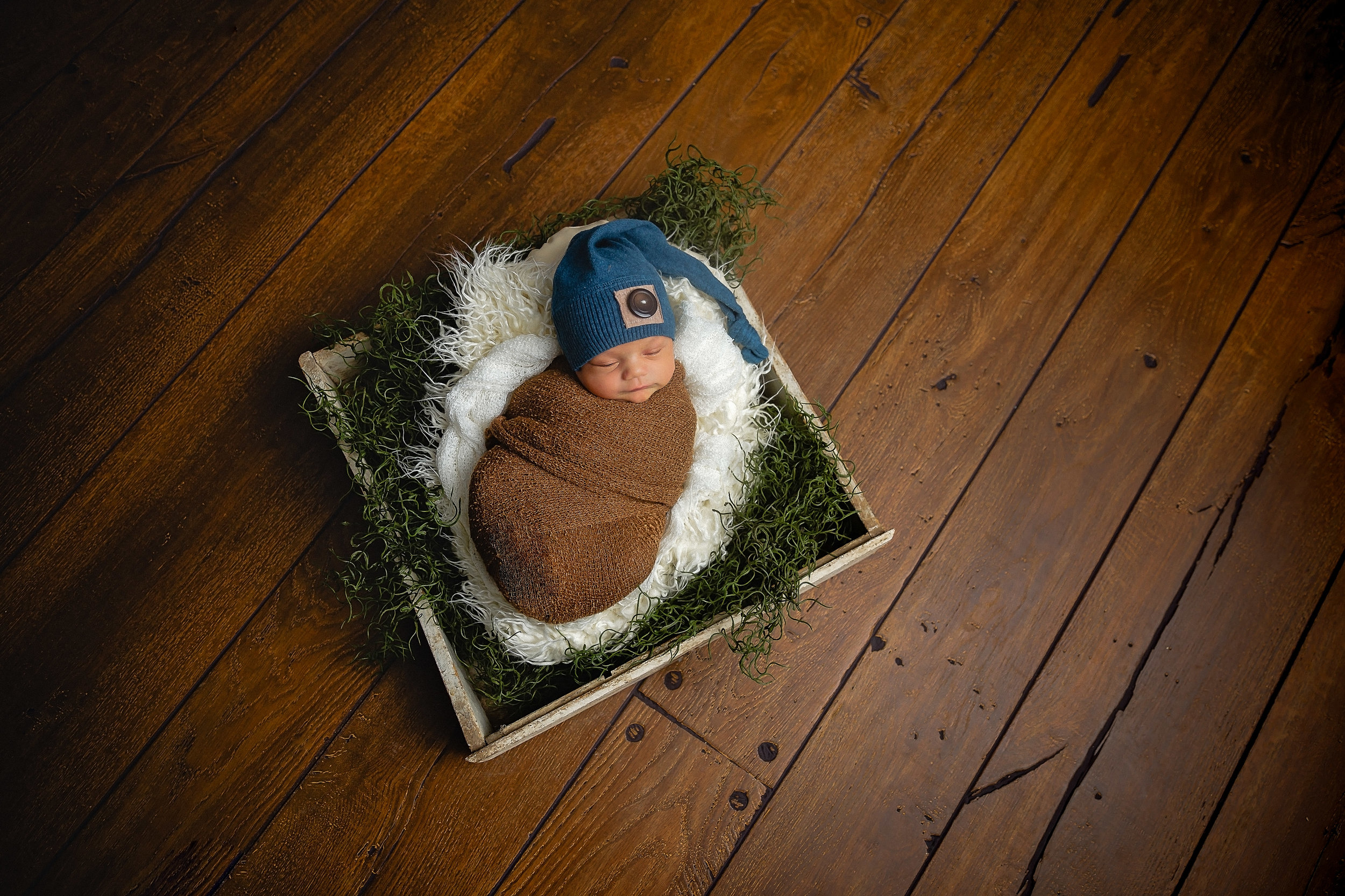baby in drawer on wood floor with moss and white fur and blue sleepy hat photographer in fort leonard wood